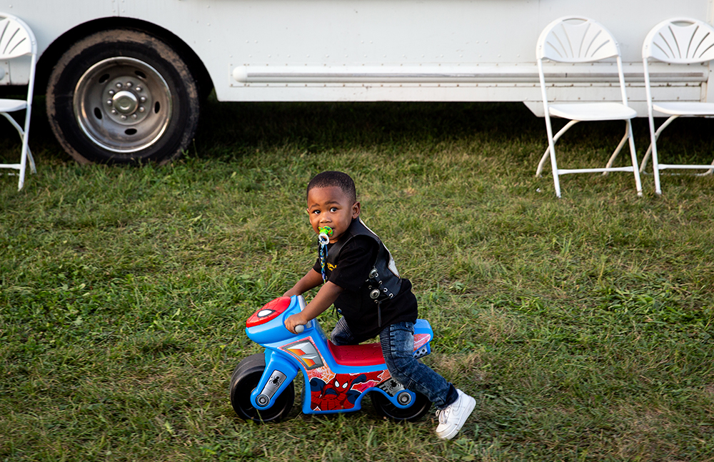 Not quite two years-old, Joshua Mitchum tools around the mile track infield on a toy motorcycle while walking with his grandfather, Dennis Barton of St.Louis, Mo. at the National Bikers Roundup Wednesday, Aug. 1, 2018 Illinois State Fairgrounds in Springfield, Ill. [Rich Saal/The State Journal-Register]