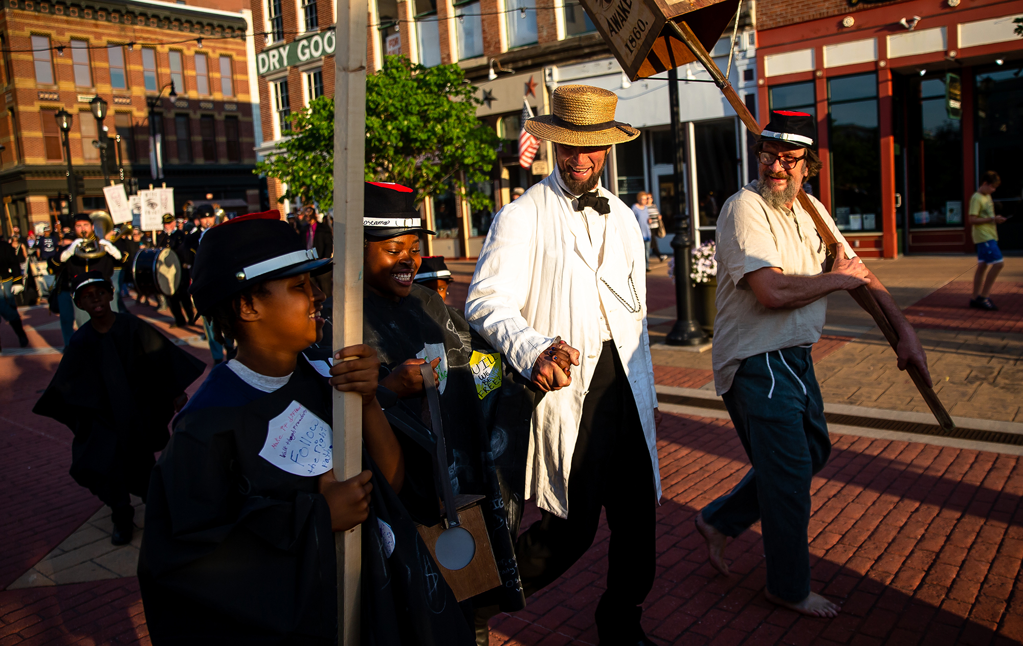 Fritz Klein portraying Abraham Lincoln is joined by youth of the Springfield Urban League, who helped make the caps and caps worn by the Wide Awakes, during the Lincoln Wide Awake Parade, a re-enactment of an 1860 parade to support Abraham LincolnÕs presidential candidacy, a march to the Old State Capitol to the the Lincoln Home, Saturday, Aug. 4, 2018, in Springfield, Ill. The Wide Awakes, who wore black caps and black hats when they marched, got their name from a small group of young self-named supporters who impressed Lincoln at a political rally, according to the Journal of American History. [Justin L. Fowler/The State Journal-Register]