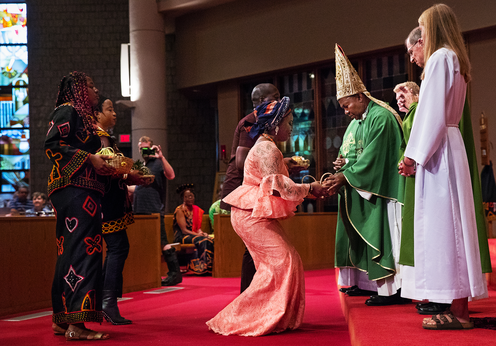Lucy Tankoua presents a basket of strawberries to Archbishop Cornelius Fontem Esua from the Archdiocese of Bamenda, Cameroon, during the offertory Sunday, July 29, 2018. The special service included music by the African Ensemble of Central Illinois, authentic African art and a meal of African food afterwards. [Ted Schurter/The State Journal-Register]