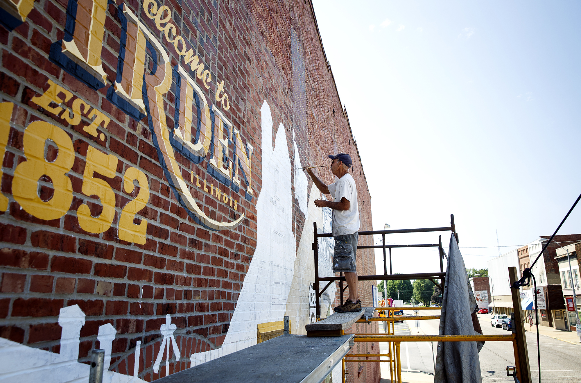 Bernie Gietl works on the new Virden History Mural on the side of the Sav-Mor Pharmacy building in Virden, Ill. Thursday, Aug. 2, 2018. Gietl and his wife, D.L. Whitlock-Gietl, are sign painters and the artists leading the project, which will include images depicting the townÕs namesake, John Virden and the Virden Hotel, its connection to the railroad, and American aviator Charles Lindbergh. Gietl says the mural should be mostly completed by the end of the weekend. [Rich Saal/The State Journal-Register]