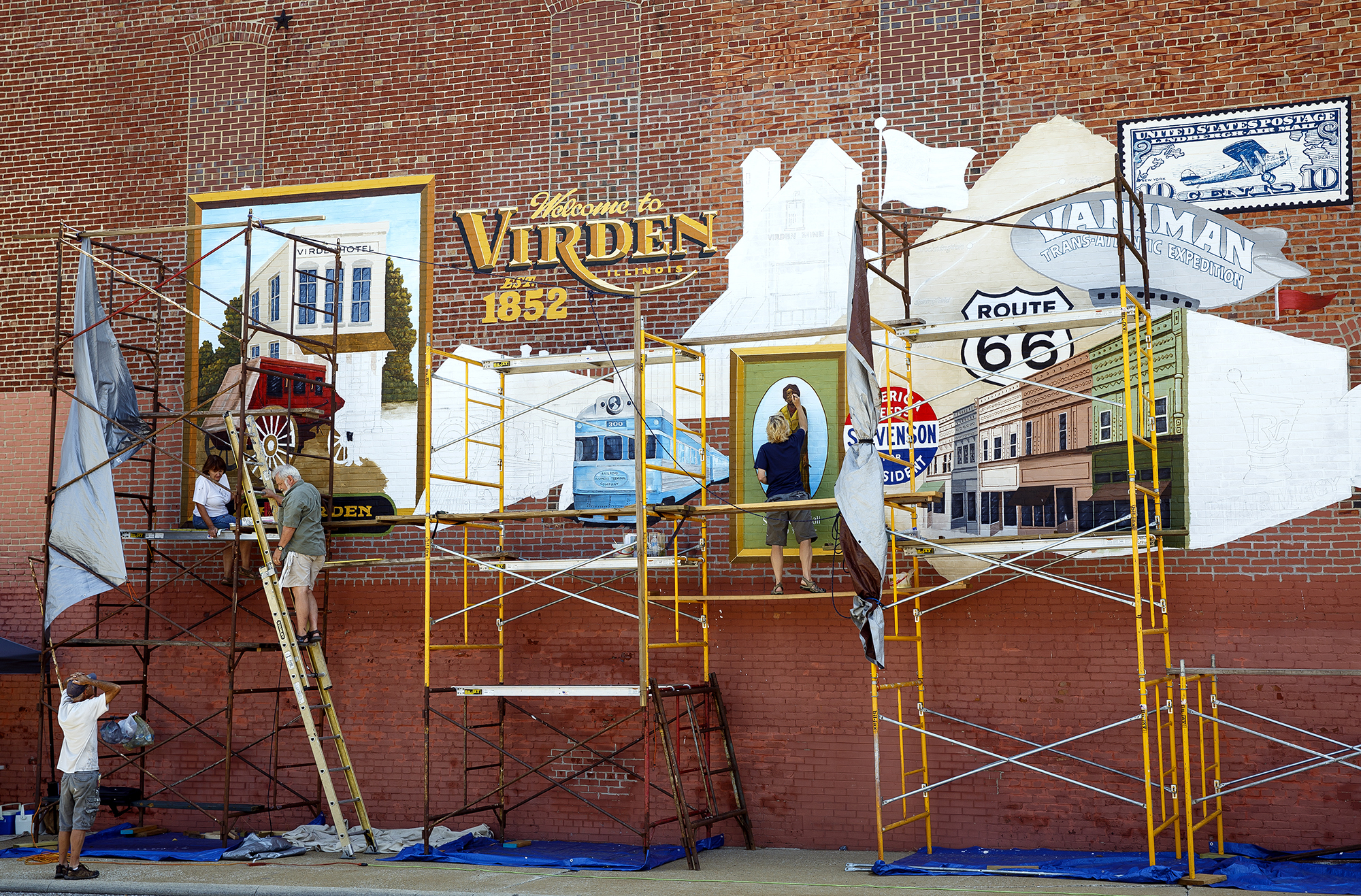 The Virden History Mural Committee raised $22,600 for the project, which measures 13 feet by 42 feet. From left, Bernie Gietl, Kathy and Tom Durham, and DL Whitlock-Gietl work on the mural Thursday, Aug. 2, 2018 on the side of the Sav-Mor Pharmacy building  in Virden, Ill. [Rich Saal/The State Journal-Register]