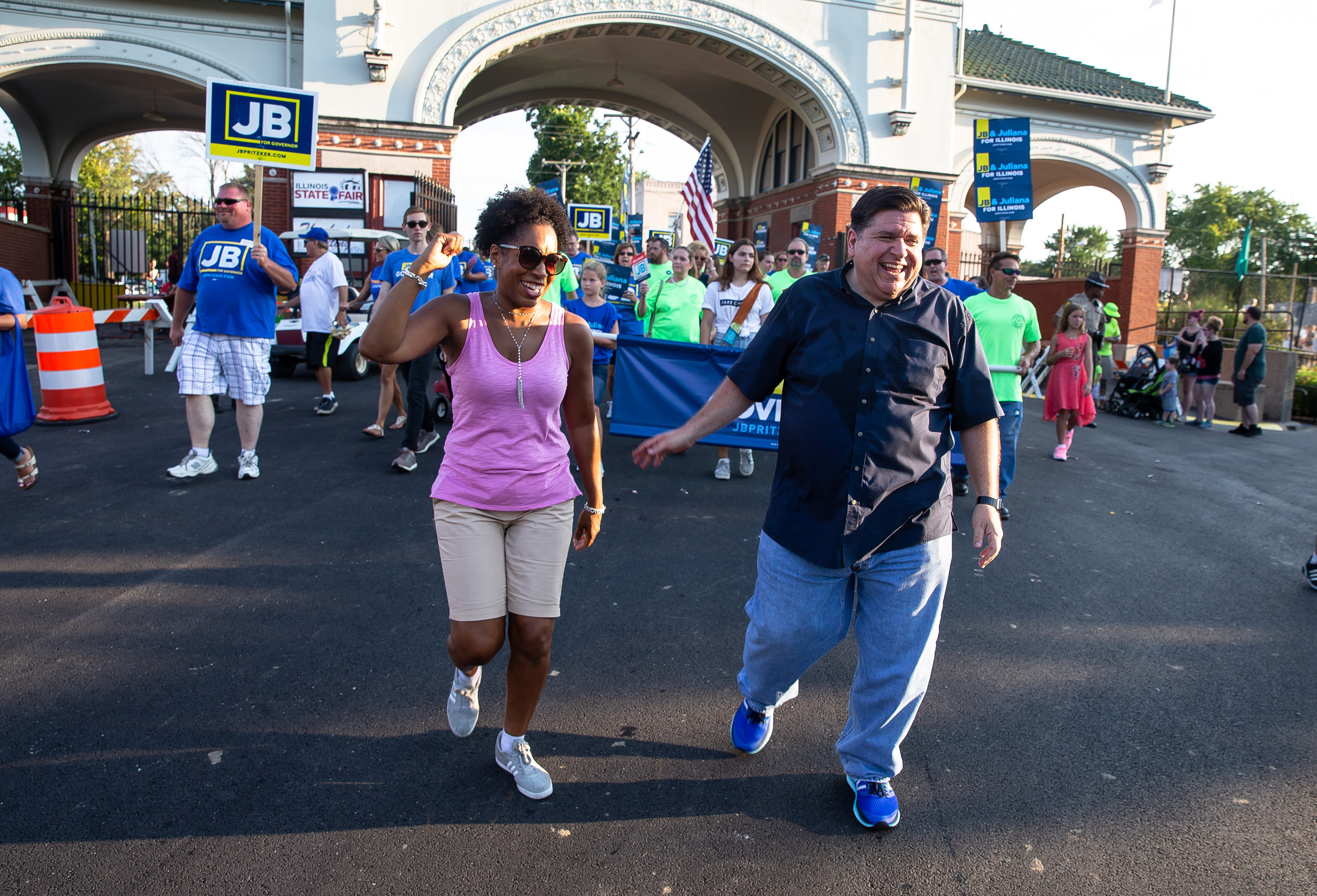 Democratic gubernatorial candidate J.B. Pritzker and his running mate Juliana Stratton enter the the Main Gate as they march during the Illinois State Fair Twilight Parade, Thursday, Aug. 9, 2018, in Springfield, Ill. [Justin L. Fowler/The State Journal-Register]