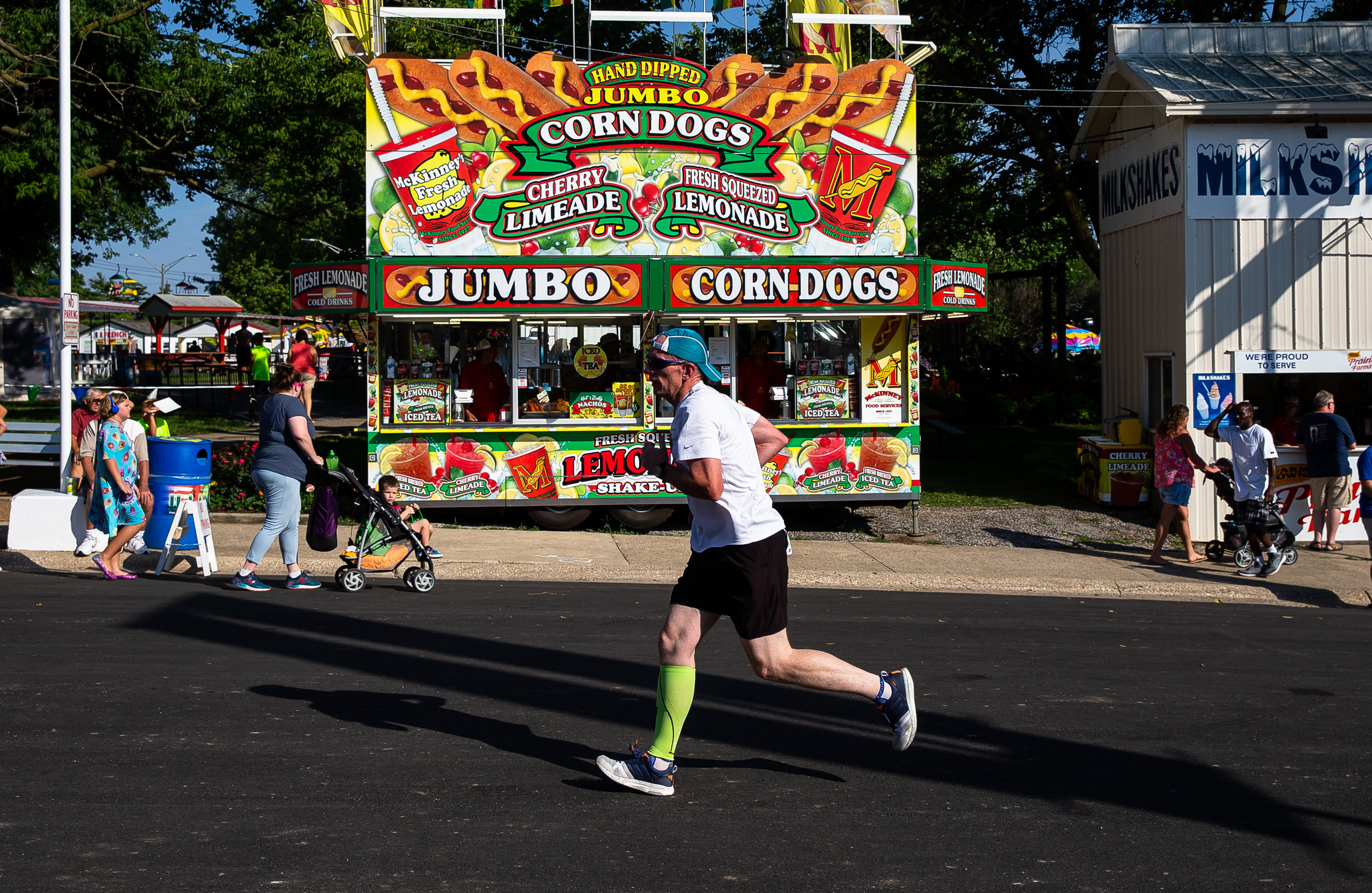 Runners in the Illinois State Fair Parade Run pass by the corn dog stand on Main Street as they near the finish line prior to the Illinois State Fair Twilight Parade, Thursday, Aug. 9, 2018, in Springfield, Ill. [Justin L. Fowler/The State Journal-Register]