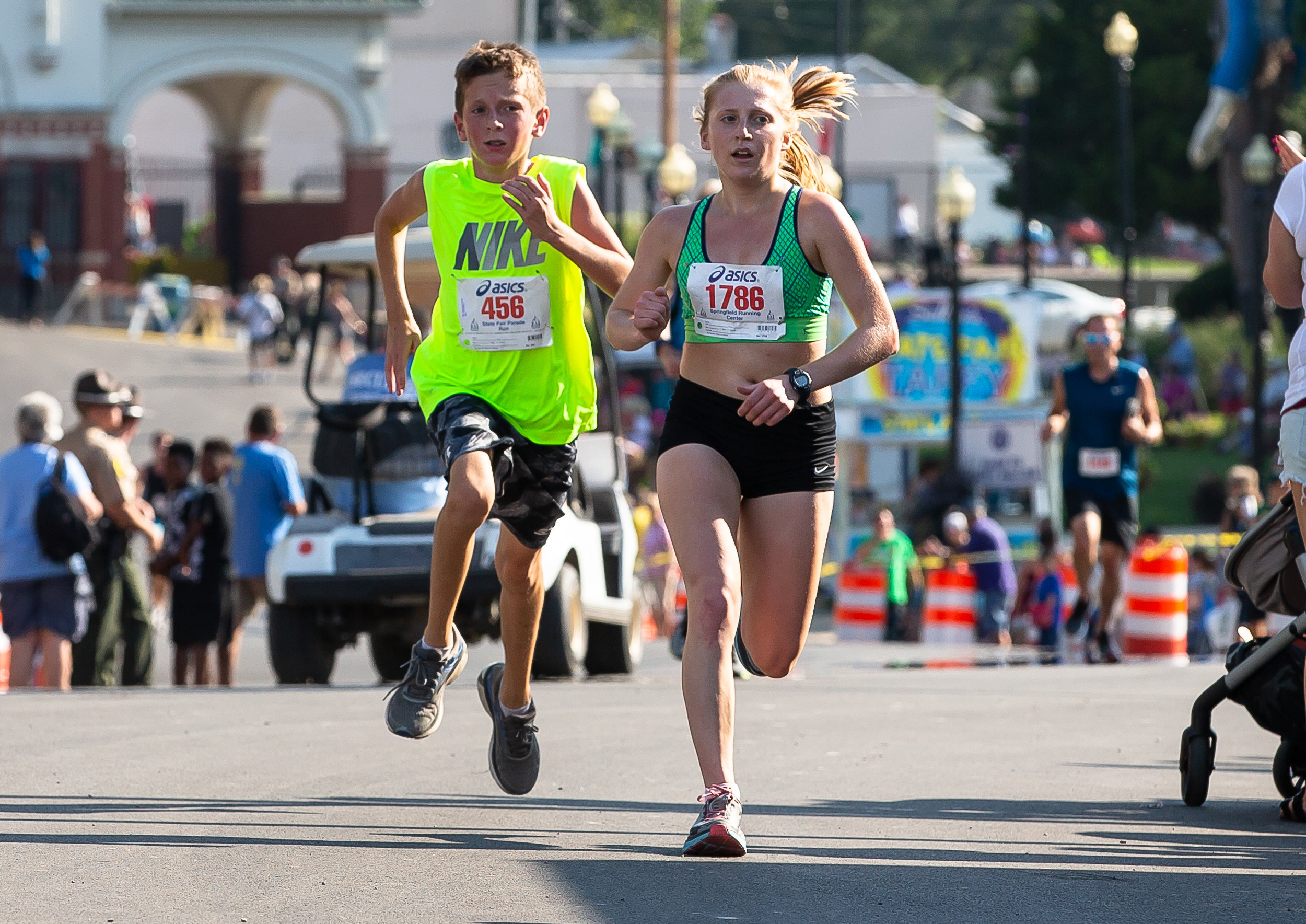 Adrienne Brauer comes to the finish line with a time of 12:08.6 to become the top female finisher in the Illinois State Fair Parade Run prior to the Illinois State Fair Twilight Parade, Thursday, Aug. 9, 2018, in Springfield, Ill. [Justin L. Fowler/The State Journal-Register]