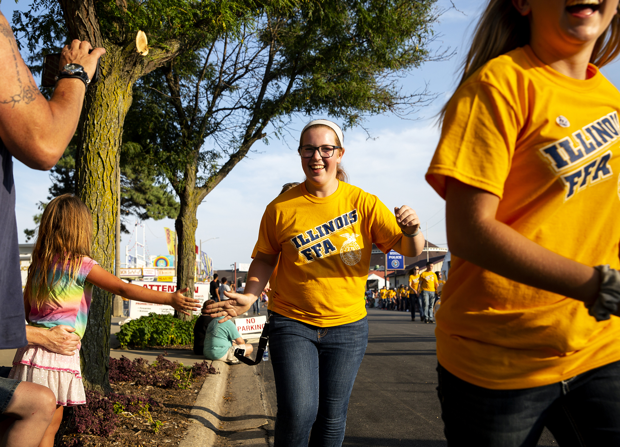 Members of the Illinois FFA exchange high-fives with Annabella Banning as they run past during the Illinois State Fair Twilight Parade Thursday, Aug. 9, 2018 on the Illinois State Fairgrounds in Springfield, Ill. [Rich Saal/The State Journal-Register]