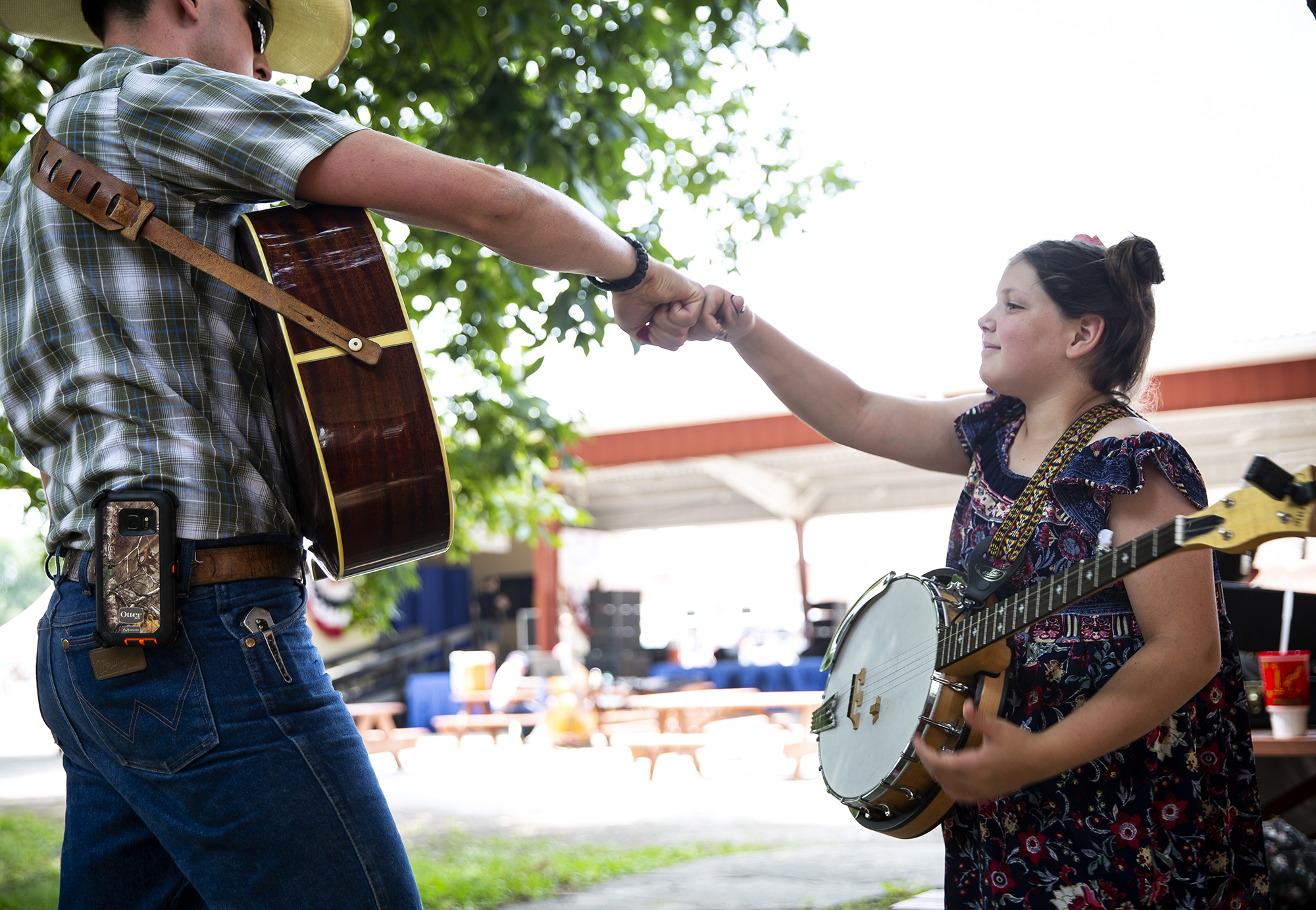 After practicing the pieces she'll play on stage, Judith Worthington gets a fist bump from her brother Matthew, a sign she's good to go for her performance in the Fiddle and Banjo Contest on the Lincoln Stage at the Illinois State Fair Saturday, Aug. 11, 2018 on the fairgrounds in Springfield, Ill. [Rich Saal/The State Journal-Register]