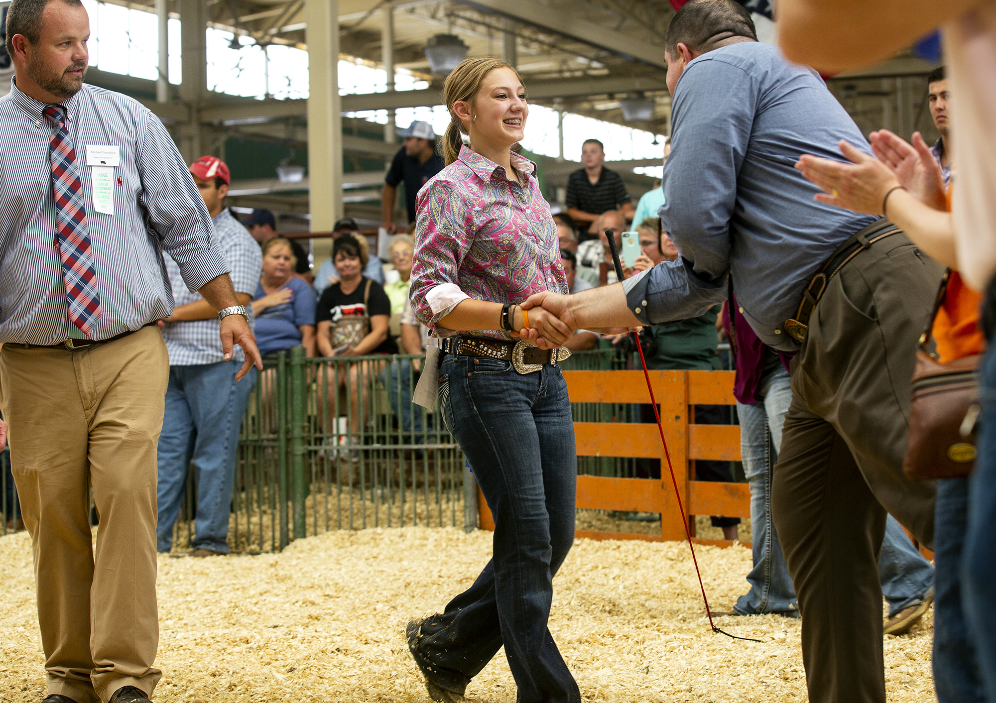 After selecting her Hampshire barrow the breed champion, the judges, Michael Gustafson, left, and John Staude congratulate Brooke Beyers of Sibley in the Land of Lincoln Junior Barrow Show at the Illinois State Fair Saturday, Aug. 11, 2018 on the fairgrounds in Springfield, Ill. [Rich Saal/The State Journal-Register]