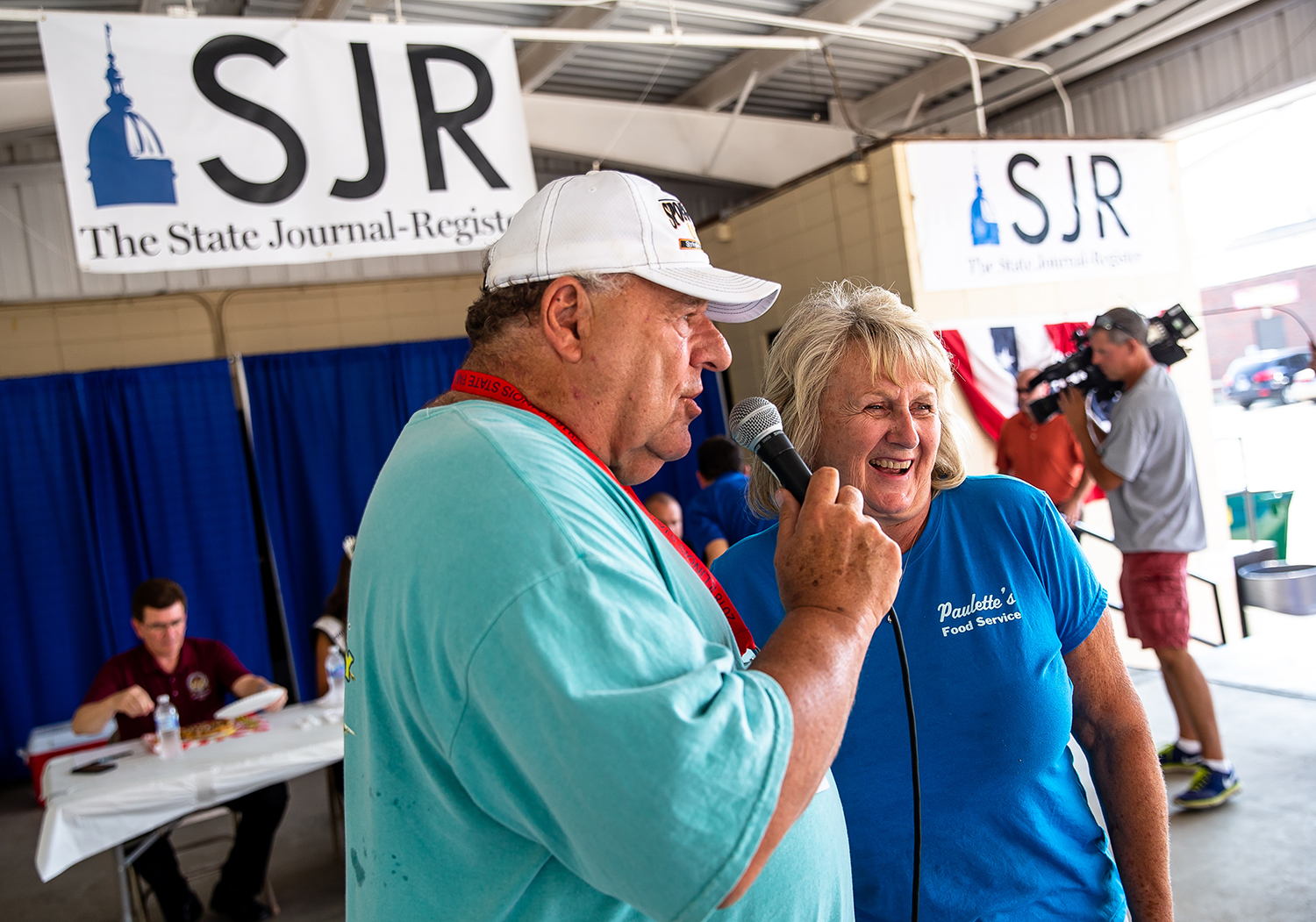 Emcee Sam Madonia talks with Paulette Keene of Paulette's Food Service from Pinckneyville, Ill., about her  turtle funnel cake in the sweet category during the judging in Golden Abe's Fantastic Fair Food competition at the Lincoln Stage at the Illinois State Fair, Friday, Aug. 10, 2018, in Springfield, Ill. [Justin L. Fowler/The State Journal-Register]