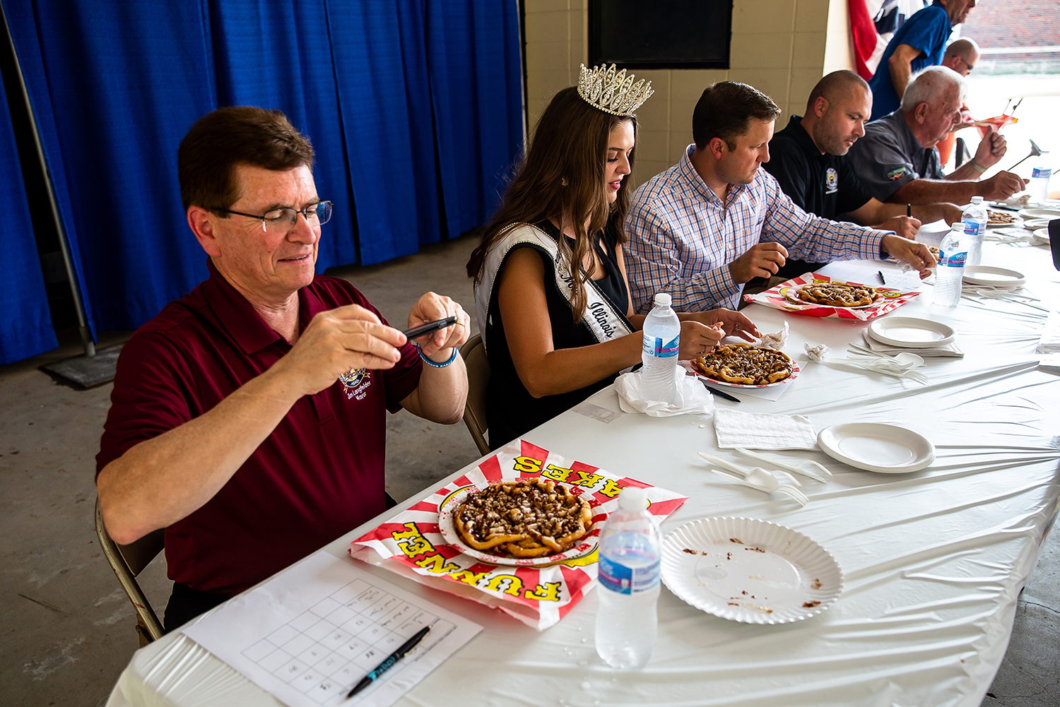 Mayor Jim Langfelder snaps a picture of the turtle funnel cake from Paulette Keene of Paulette's Food Service during the judging for the sweet category in the Golden Abe's Fantastic Fair Food competition at the Lincoln Stage at the Illinois State Fair, Friday, Aug. 10, 2018, in Springfield, Ill. [Justin L. Fowler/The State Journal-Register]