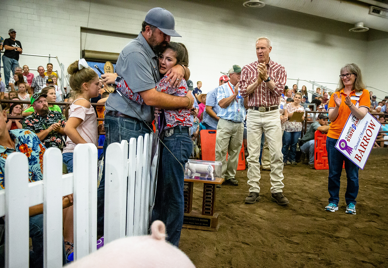 Ella Bobell, 12, hugs her father, Ben, after winning the Grand Champion Barrow during the Parade of Champions at the Livestock Center during the Illinois State Fair at the Illinois State Fairgrounds, Saturday, Aug. 11, 2018, in Springfield, Ill. [Justin L. Fowler/The State Journal-Register]