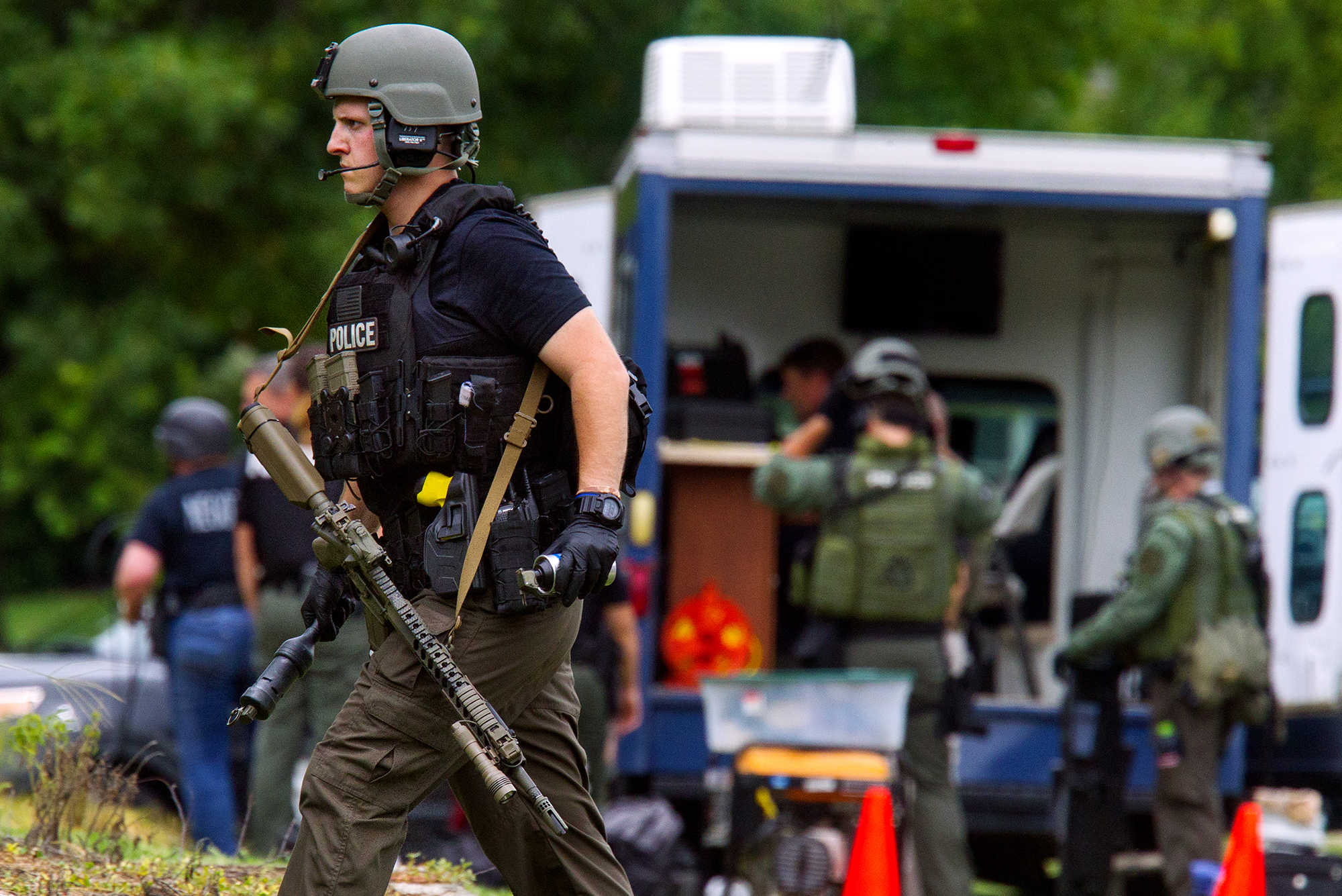 A Springfield Police officer moves into position during a nearly six-hour standoff at an apartment complex on Seven Pines Road in Springfield Tuesday, Aug. 7, 2018. [Ted Schurter/The State Journal-Register]