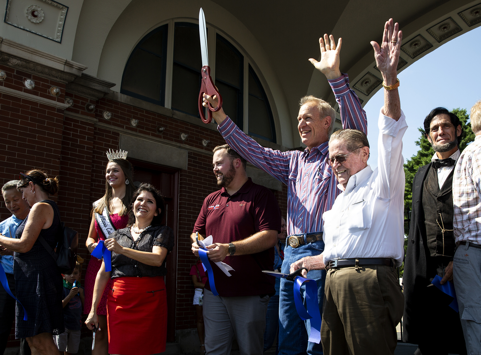 Gov. Bruce Rauner cuts the ribbon to officially open the 2018 Illinois State Fair Thursday, Aug. 9, 2018 on the Illinois State Fairgrounds in Springfield, Ill. With the governor are, from left, Miss Illinois County Fair Queen Samantha Hasselbring, Lt. Gov. Evelyn Sanguinetti, Illinois State Fair manager Luke Sailer, Gov. Rauner, and Robert Wiseman, State Fair Twilight Parade grand marshal. [Rich Saal/The State Journal-Register]