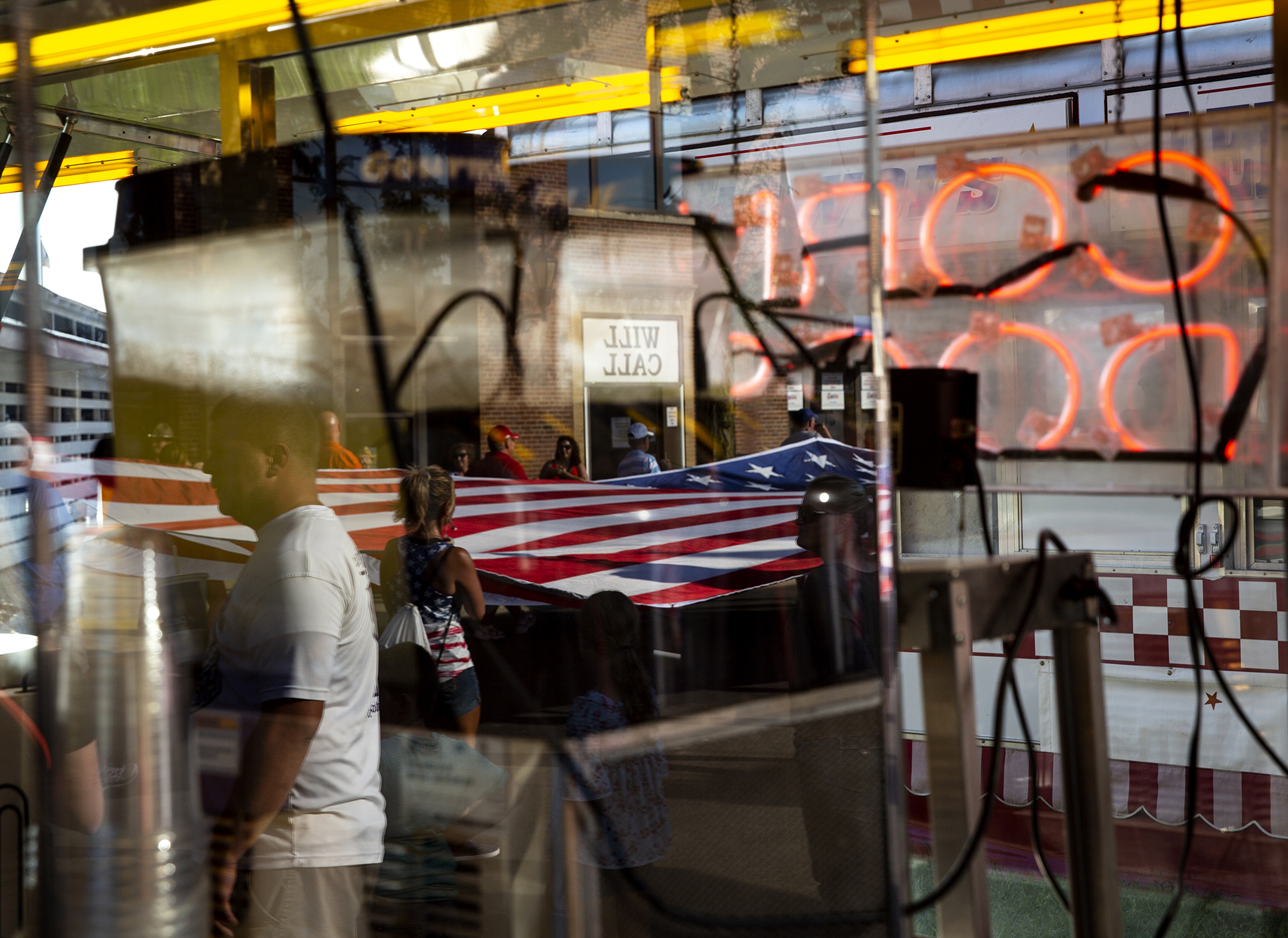 An American flag presented by the Illinois Elks Lodge 158 in Springfield and carried through the fairgrounds, is reflected in a concession stand during the Illinois State Fair Twilight Parade Thursday, Aug. 9, 2018 on the Illinois State Fairgrounds in Springfield, Ill. [Rich Saal/The State Journal-Register]