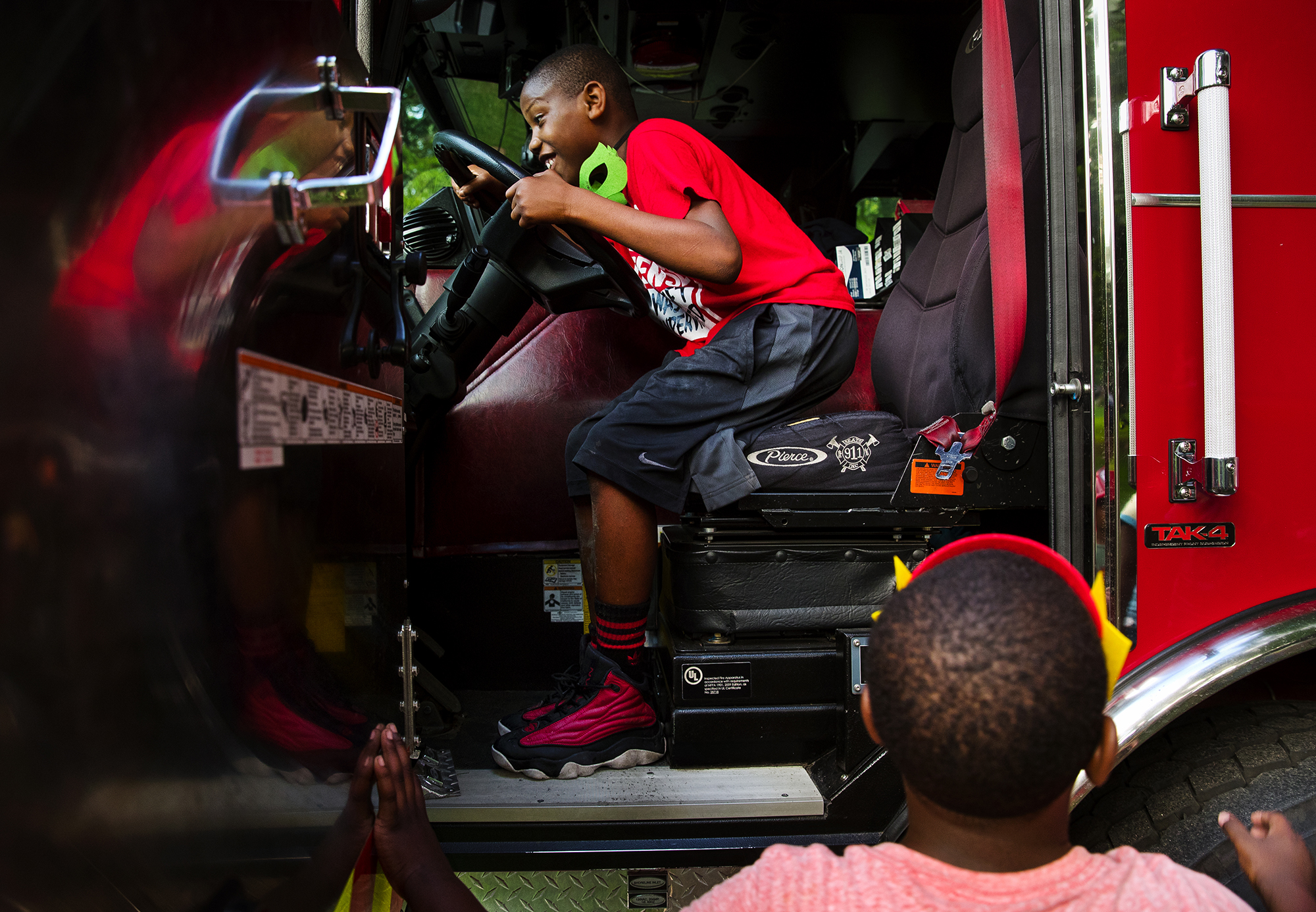Christian Duncan gets behind the wheel of Springfield Fire Department's Engine Four from Station Four during a National Night Out event at Enos Park Tuesday, Aug. 7, 2018. Multiple events took place across Springfield to promote community-building, camaraderie and to make neighborhoods safer, more caring places to live. [Ted Schurter/The State Journal-Register]