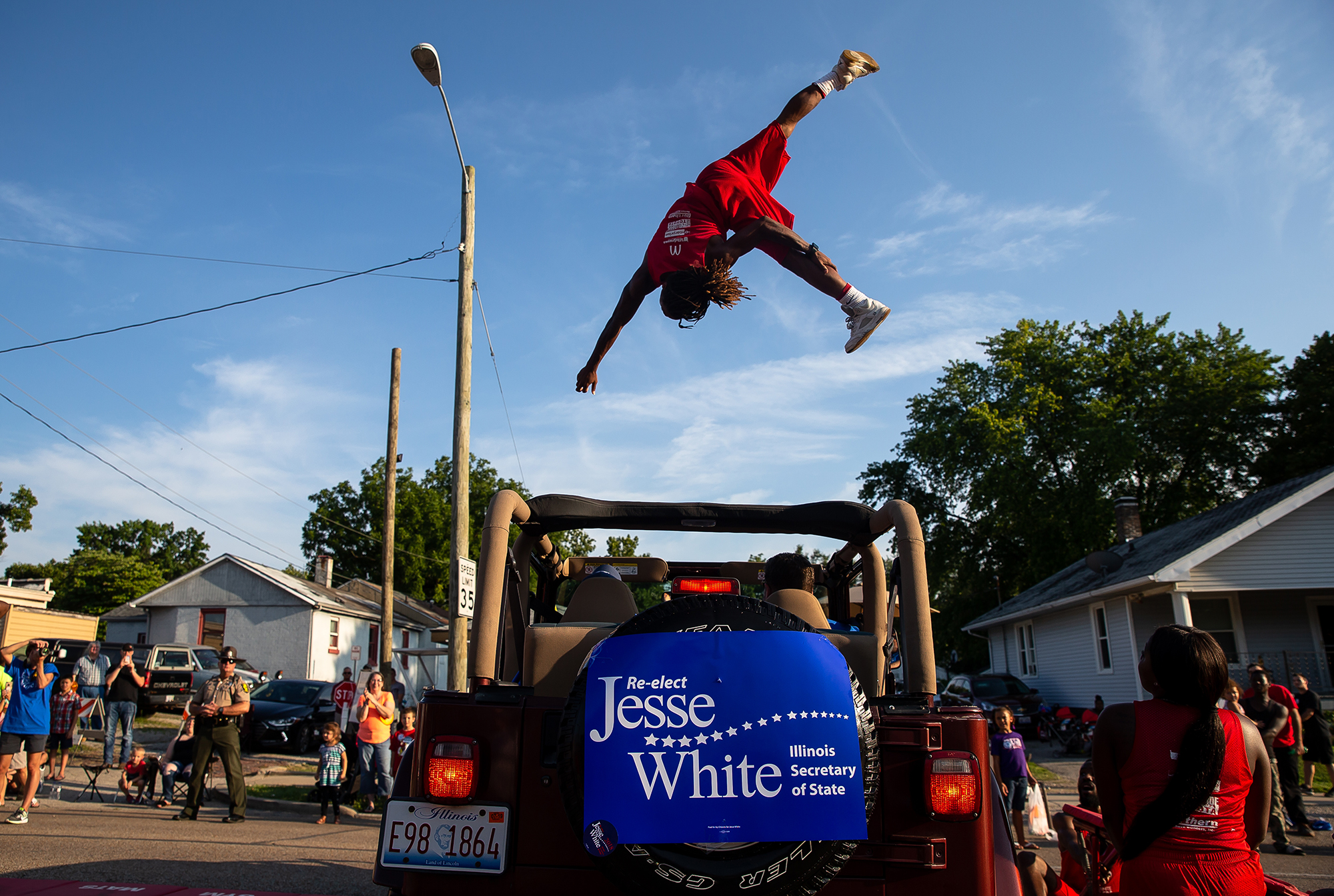 Corey Bell, of Chicago, Ill., leaps over a Jeep Wrangler as he performs with Illinois Secretary of State Jesse White and the Tumblers during the Illinois State Fair Twilight Parade, Thursday, Aug. 9, 2018, in Springfield, Ill. [Justin L. Fowler/The State Journal-Register]
