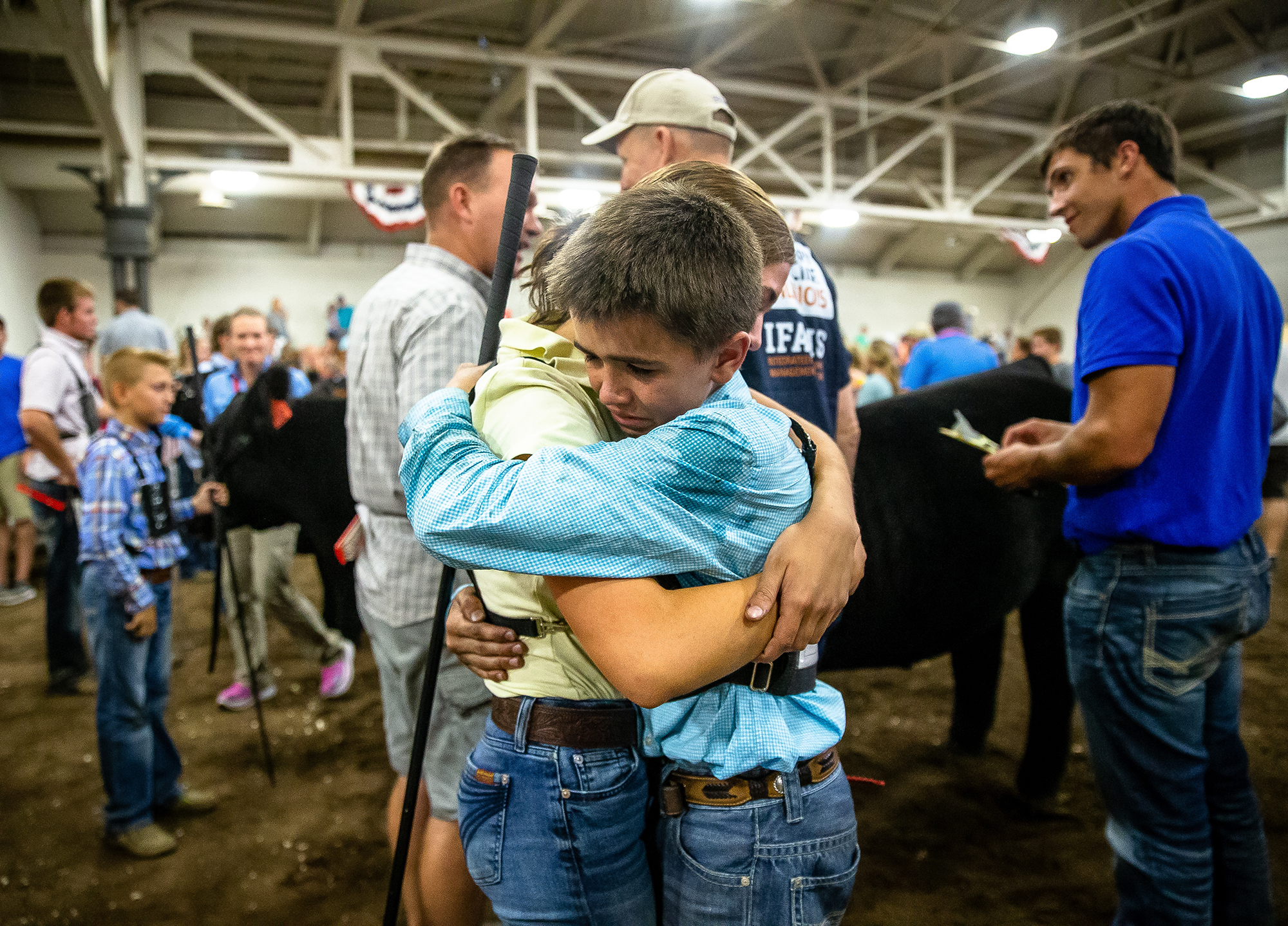"""Adam MIller hugs his sister, Amelia, after his Crossbred named """"Taco"""" won Grand Champion steer during the Parade of Champions at the Livestock Center during the Illinois State Fair at the Illinois State Fairgrounds, Saturday, Aug. 11, 2018, in Springfield, Ill. [Justin L. Fowler/The State Journal-Register]"""