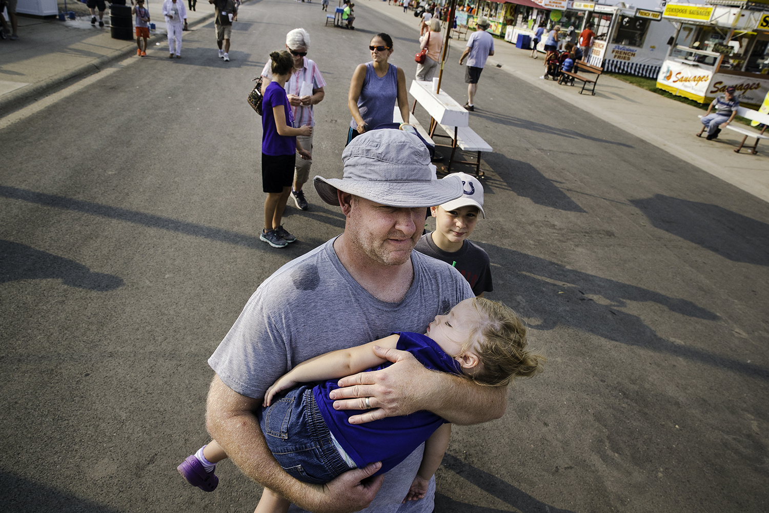 Josh Swift carries his daughter Iris as she naps while the family strolls down Grandstand Avenue at the Illinois State Fair Monday, Aug. 13, 2018. [Ted Schurter/The State Journal-Register]
