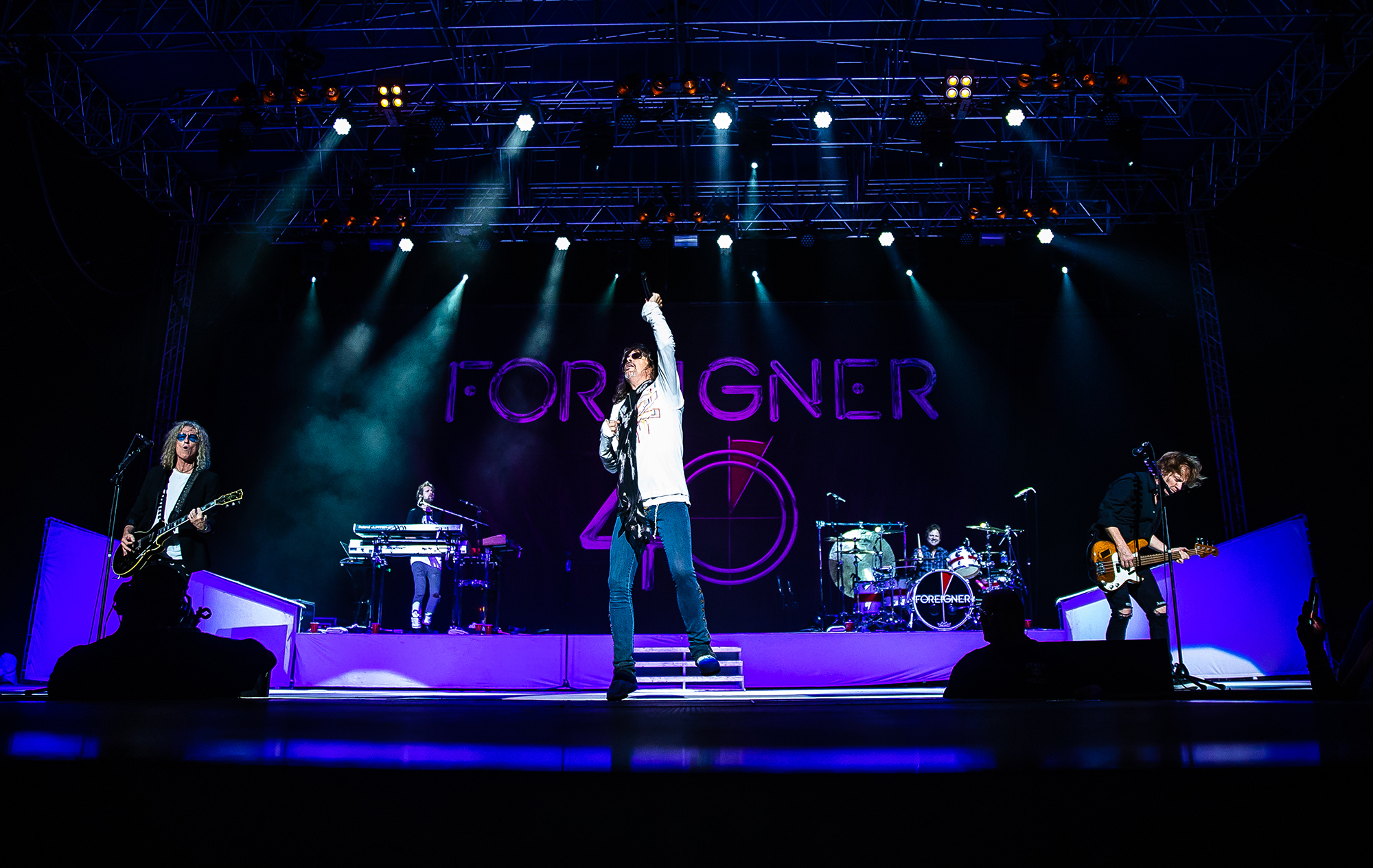 Lead singer Kelly Hansen, center, guitarist Bruce Watson, left, and bassist Jeff Pilson, right, perform with Foreigner as the band plays on the Grandstand Stage during the Illinois State Fair at the Illinois State Fairgrounds, Sunday, Aug. 12, 2018, in Springfield, Ill. [Justin L. Fowler/The State Journal-Register]