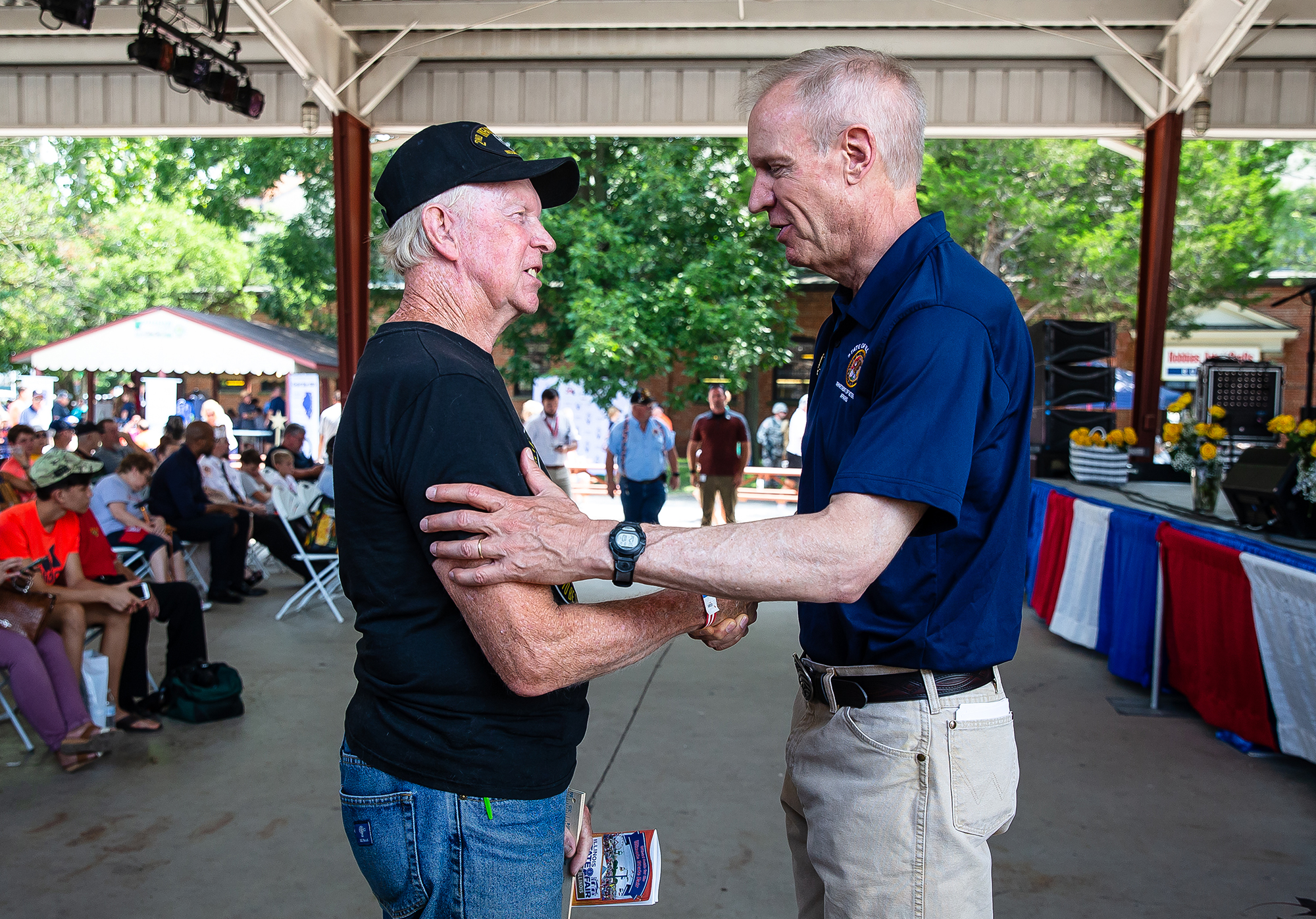 Illinois Governor Bruce Rauner visits with Army Veteran Leroy Ramthun, of Cornland, Ill., during Veterans Day program at the Illinois State Fair on the Lincoln Stage at the Illinois State Fairgrounds, Sunday, Aug. 12, 2018, in Springfield, Ill. [Justin L. Fowler/The State Journal-Register]
