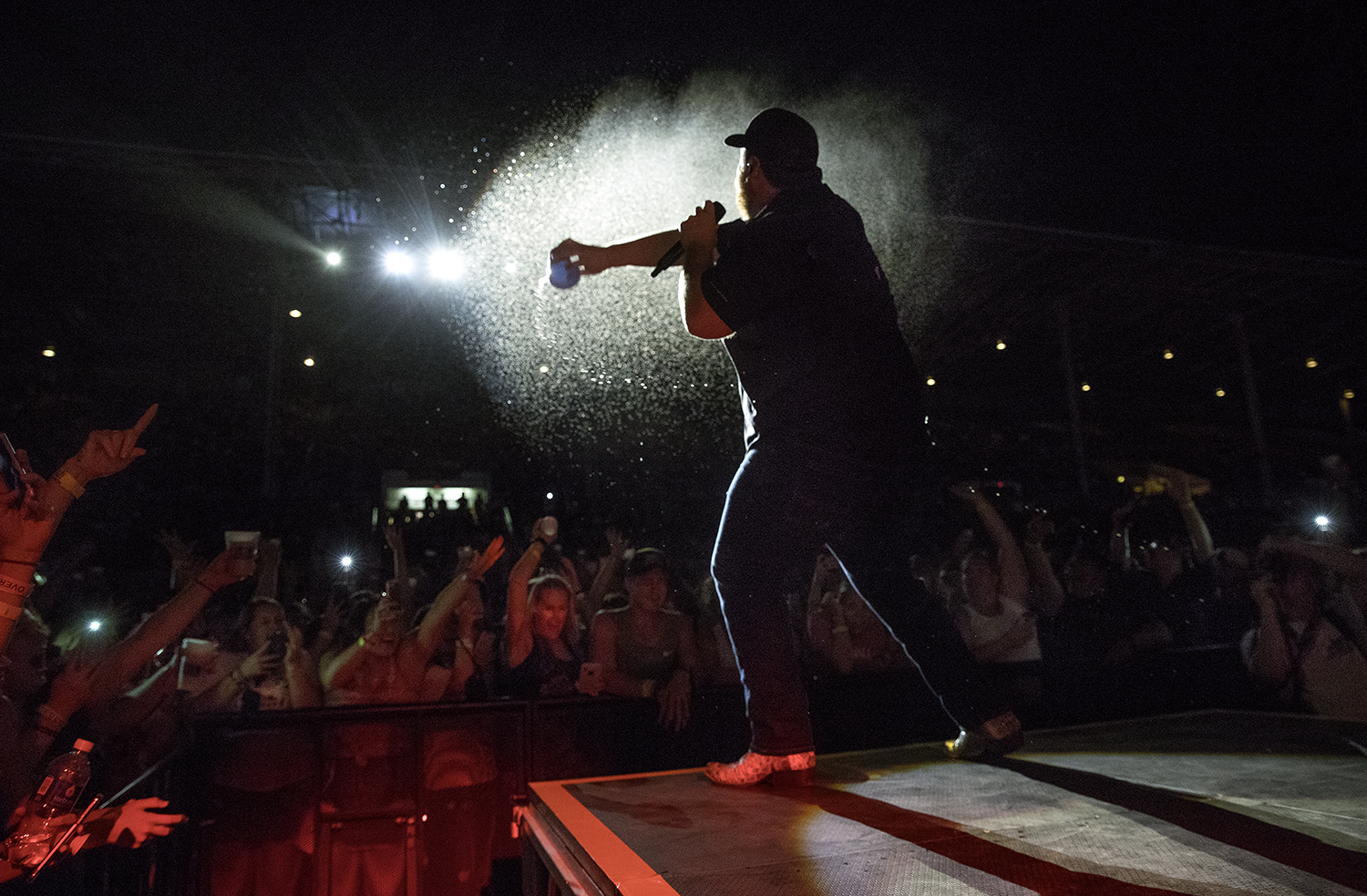 Country artist Luke Combs, right, flings his drink at the fans in the front row as he performs at the Grandstand during the Illinois State Fair Tuesday, Aug. 14, 2018. [Ted Schurter/The State Journal-Register]