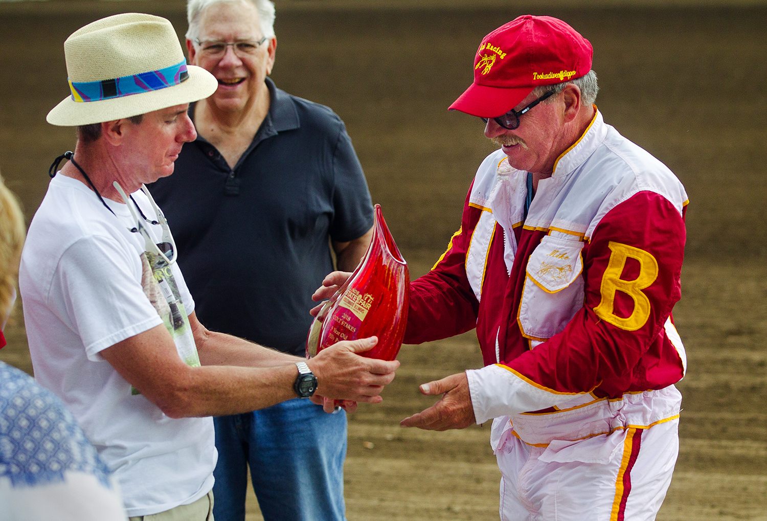 Mark Brown hands trainer Mike Brink the trophy after Michael Oosting drove their horse Allbeastnobeauty to a win in the Illinois State Fair Colt Stakes Championship 3 year-old Fillies at the Illinois State Fair Wednesday, Aug. 15, 2018. The horse is owned locally by Brink, Brown and Josh Carter. [Ted Schurter/The State Journal-Register]