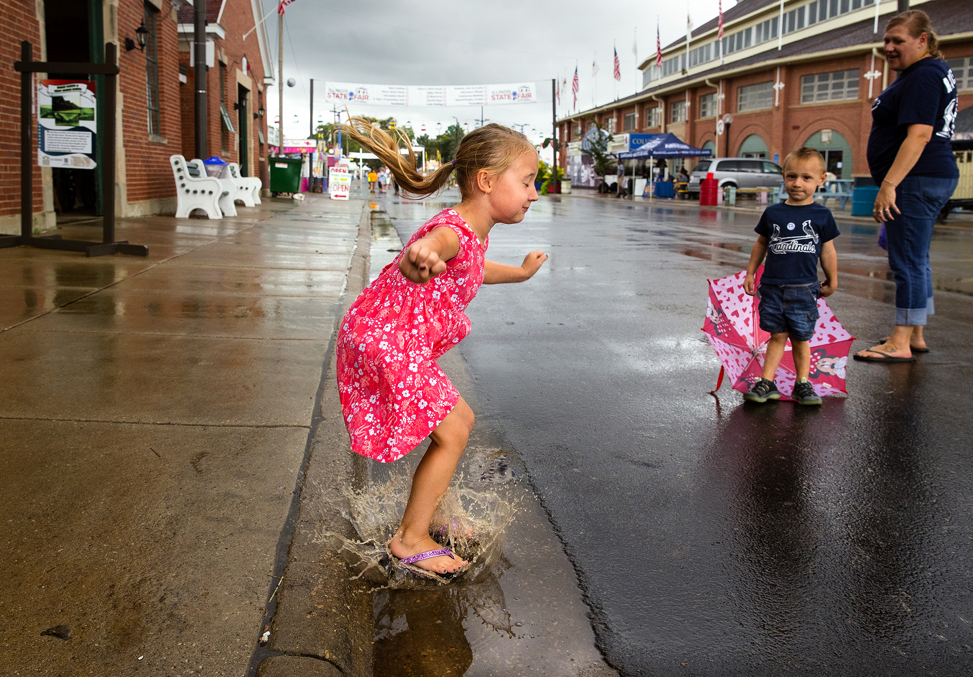 Jeslyn Taylor leaps into a puddle as a light rain falls at the Illinois State Fair Wednesay, Aug. 15, 2018. Taylor, five-years-old, was visiting with her brother Asher and mother Amanda. [Ted Schurter/The State Journal-Register]