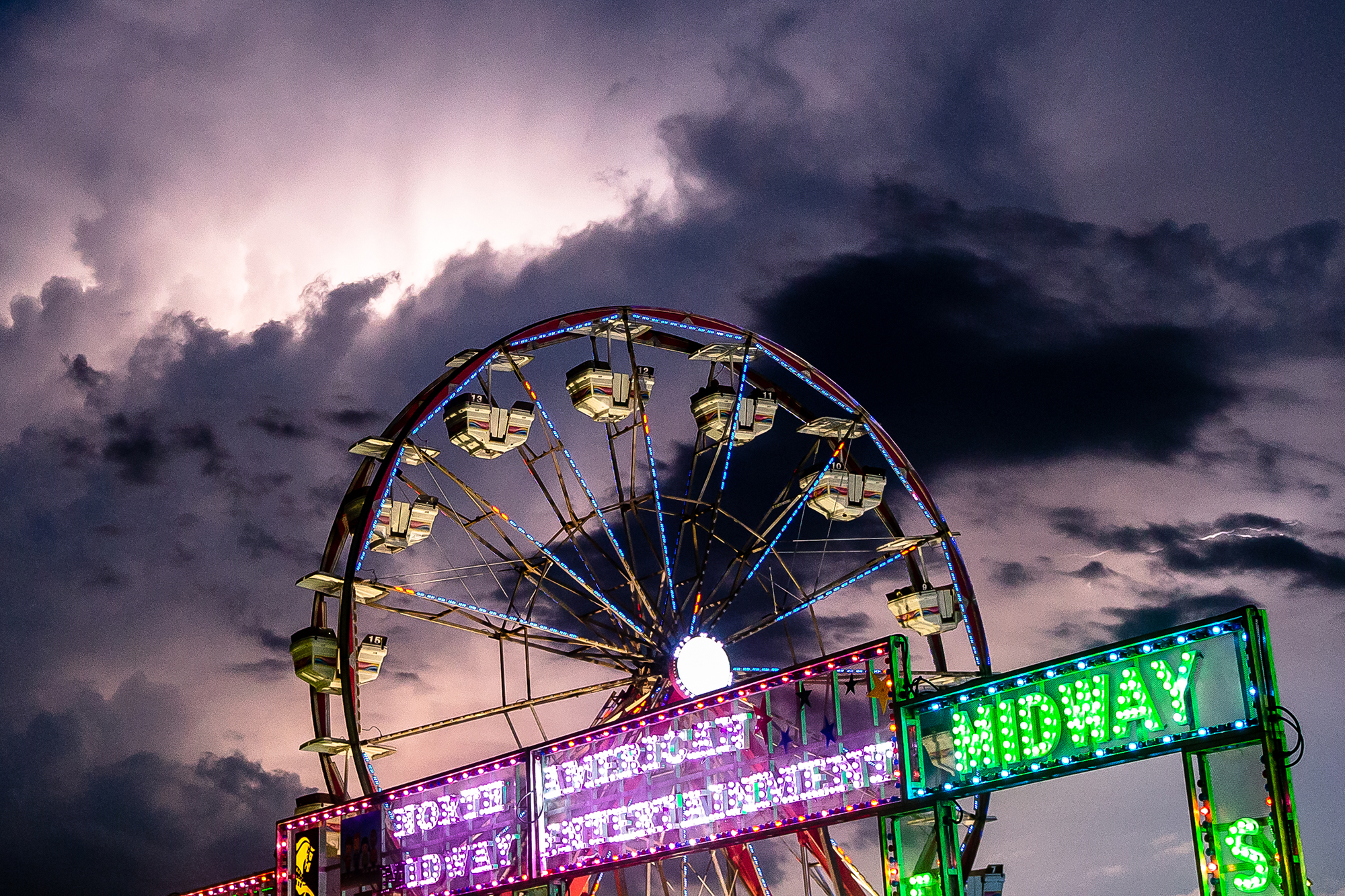 Lightning fills the sky as a backdrop to the Carnival Midway during the Illinois State Fair at Illinois State Fairgrounds, Thursday, Aug. 16, 2018, in Springfield, Ill. [Justin L. Fowler/The State Journal-Register]