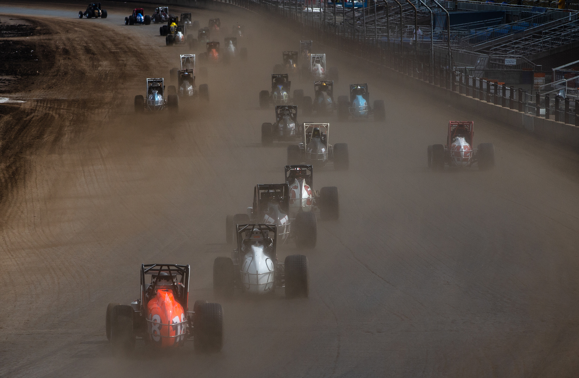 Racers disappear into a cloud of dirt on a restart after a caution as they head down the front stretch during the USAC Silver Crown Bettenhausen 100 on the Springfield Mile during the Illinois State Fair at the Illinois State Fairgrounds, Saturday, Aug. 18, 2018, in Springfield, Ill. [Justin L. Fowler/The State Journal-Register]