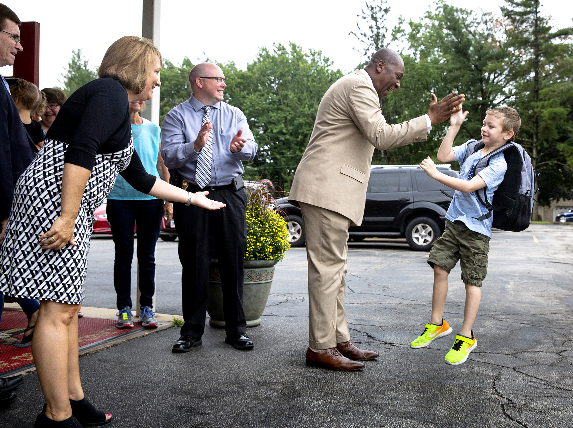 Colton Bowdern, a first grader at Hazel Dell Elementary School, connects with Jamar Scott, the school principal, for a leaping high five on the first day of classes for District 186 schools Monday, Aug. 20, 2018 at Hazel Dell Elementary School in Springfield, Ill. Faculty members and local officials, including Mayor Jim Langfelder, left, School Superintendent Jennifer Gill and Sgt. Derek Wheeler from the Springfield Police Department, were on hand to greet each student. [Rich Saal/The State Journal-Register]