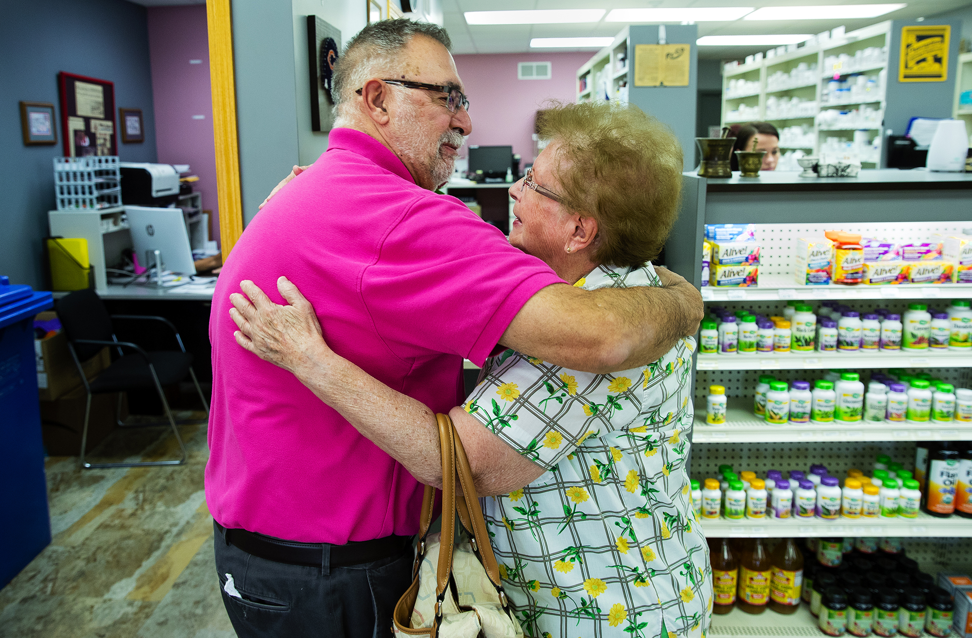 Bruce Stacy, 69, co-owner of Stacy's Family Pharmacy in Lincoln, gets a hug from longtime customer JoAnne Marlin during the last afternoon of operations at the business Wednesday, Aug. 22, 2018. [Ted Schurter/The State Journal-Register]