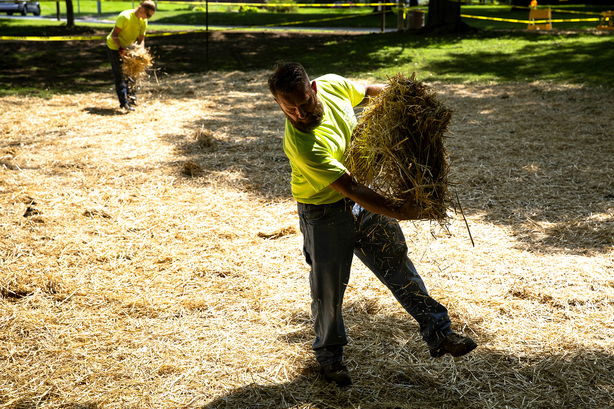 Tim Wagoner, foreground, and Tyler Landess, Springfield Park District employees, spread straw over grass seed near a new walking path under construction in Washington Park at MacArthur Boulevard Thursday, Aug. 23, 2018 in Springfield, Ill. The new concrete path replaces an old asphalt one that allows joggers and walkers a place to turn without using the sidewalk along MacArthur. It should be finished by the end of next week. [Rich Saal/The State Journal-Register]