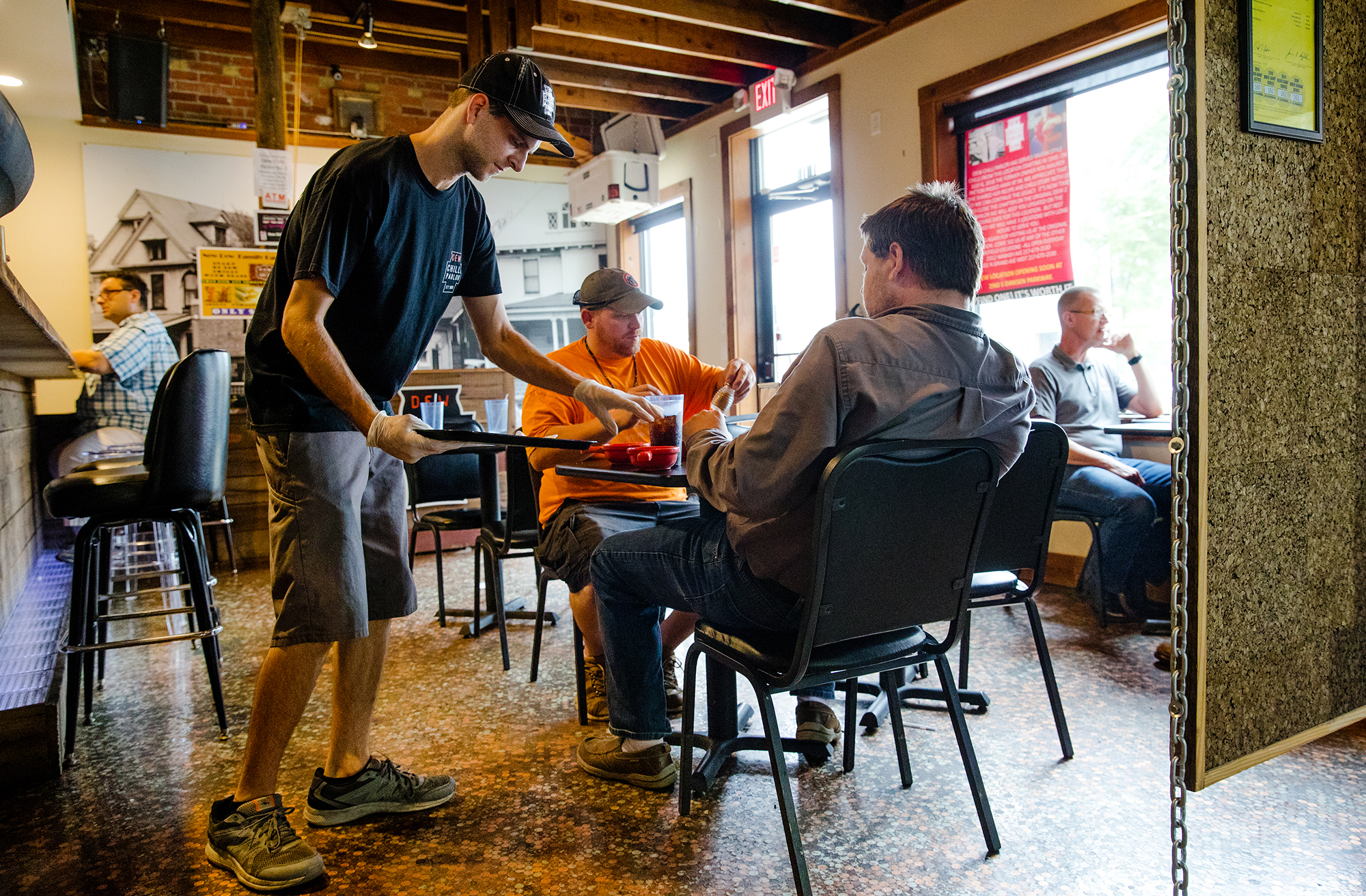 Nik Lalley serves customers Justin Metelco, left, and Cory Taylor during the last day of operation for the Dew Chilli Parlor's Fifth Street location Friday, Aug. 24, 2018. The business will continue to operate at two other Springfield locations. [Ted Schurter/The State Journal-Register]