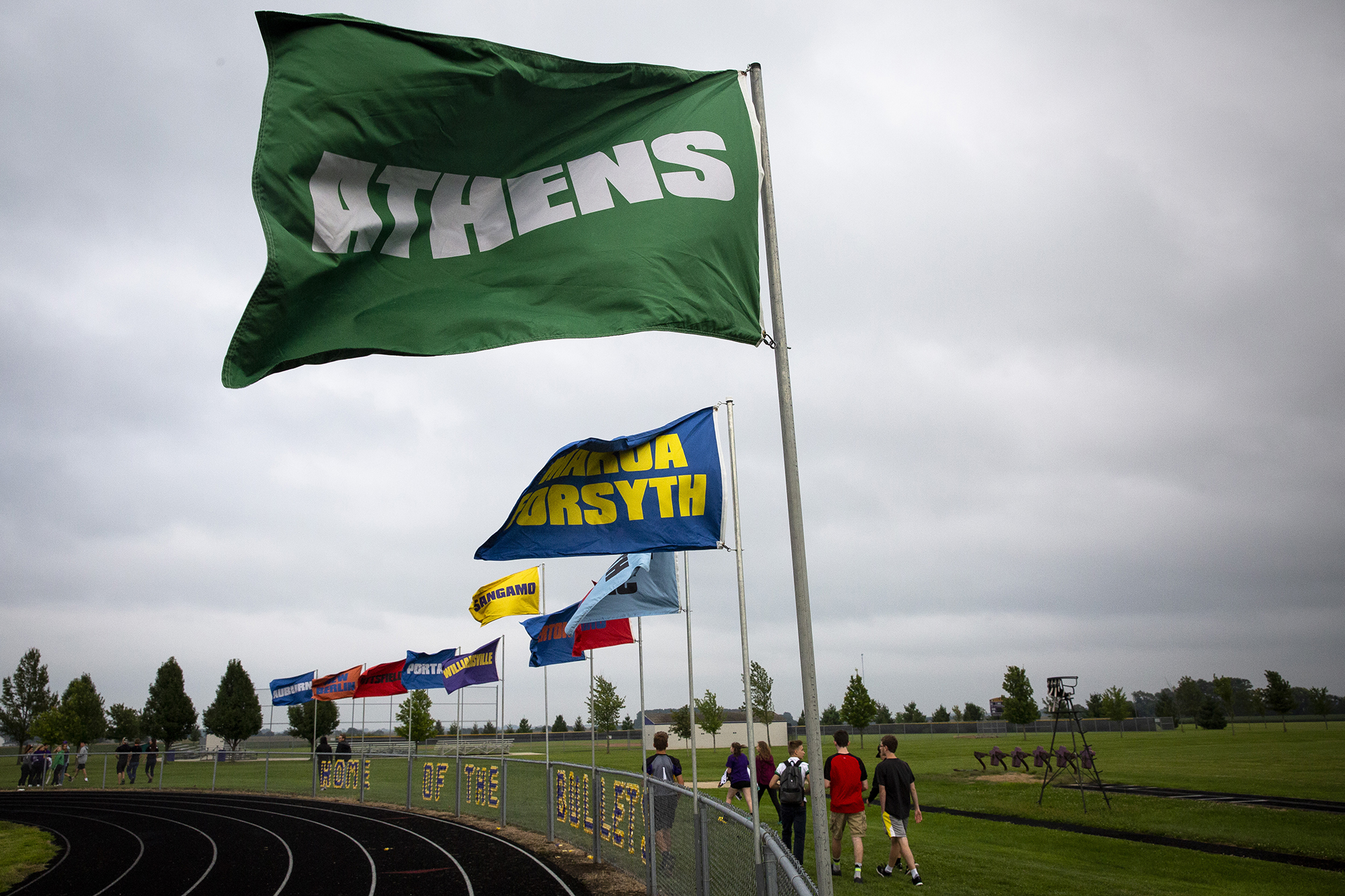 A stiff south wind straightens the flags of the Sangamo Conference teams on Paul Jenkins Field at Williamsville High School before the season-opening game between the Bullets and the Athens Warriors Friday, Aug. 24, 2018 in Williamsville, Ill. [Rich Saal/The State Journal-Register]