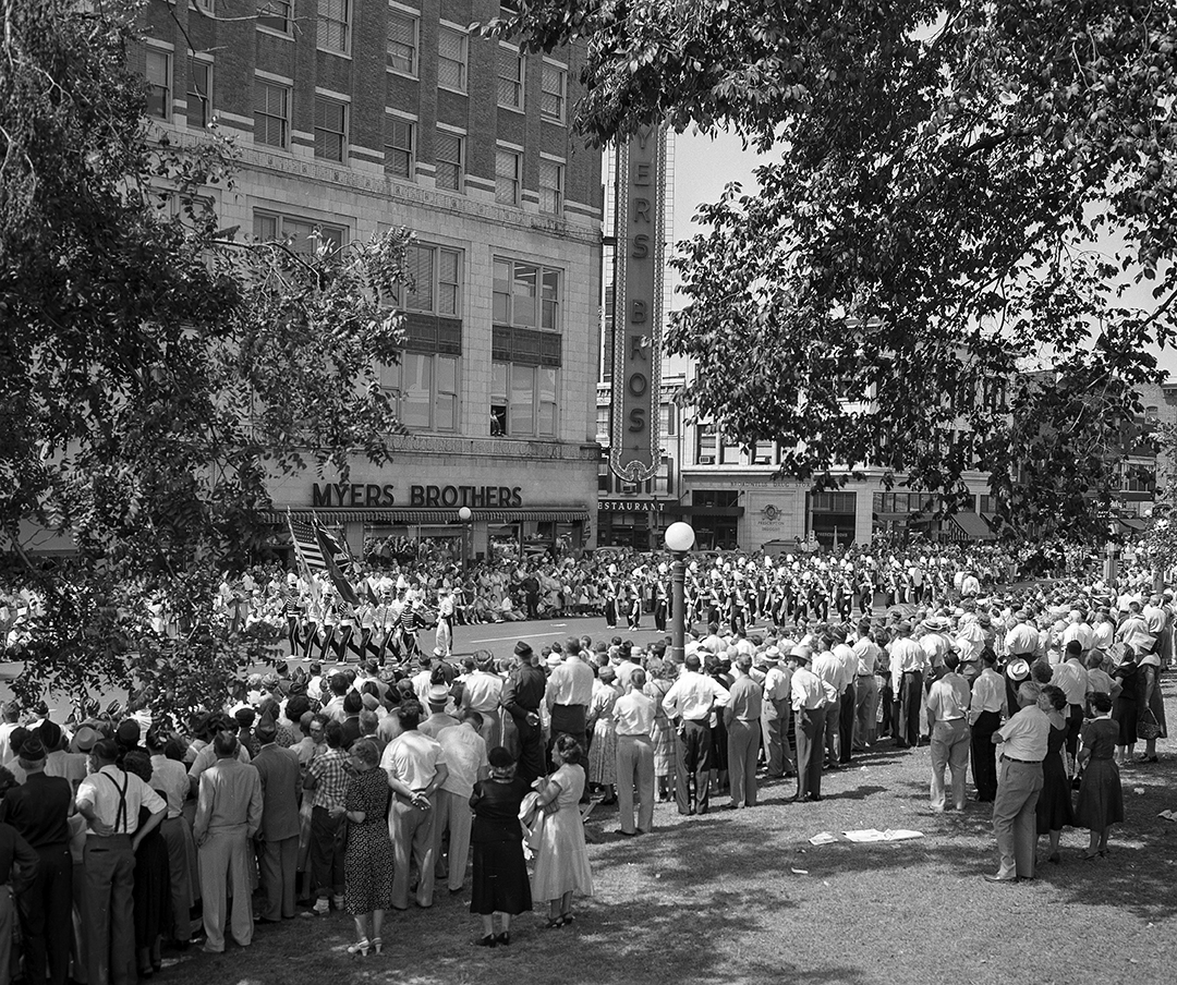 """Illinois American Legion parade on Fifth Street in front of Myers Bros. building, downtown Springfield, Ill., Sept. 4, 1955. File/The State Journal-Register picpast; spihistory; parade; military; veterans; architecture; Published as Picturing the Past, Sept. 2, 2018:It wasn't a Labor Day parade, per se, even though it was held on Labor Day weekend in September 1955. The """"Big Parade,"""" as it was called, coming at the end of the Illinois American Legion's four day convention, was still """"spectacular,"""" according to the Illinois State Journal. The day's high temperature was in the mid 90s, but the Journal estimated 60,000 spectators lined the streets, some watching from open windows in the surrounding buildings, and stayed for the two and a half hour ordeal. Included in the parade were units from the state's more than 1,100 Legion posts, a marching band from Chanute Air Force Base, drum majorettes from Springfield's Carver trade school (first place winners at that year's Illinois State Fair competition), and an all-female drum and bugle corps from East Alton. Members of the Stockyards post in Chicago played bagpipes and wore Scotch plaid kilts. While the Springfield Municipal Band played in front of the reviewing stand on Fifth Street, three fighter bombers flew in formation overhead. File/The State Journal-Register"""