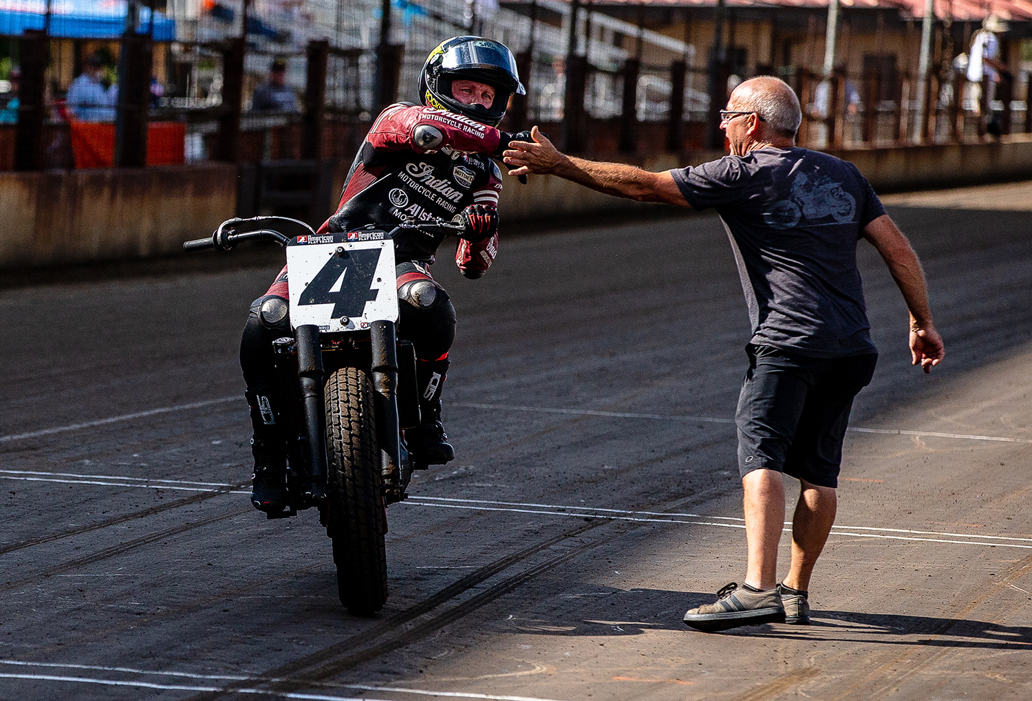 Bryan Smith gets a high five as he brings his Indian Scout FTR750 around for a victory lap after winning the American Flat Track Springfield Mile II at the Illinois State Fairgrounds, Sunday, Sept. 2, 2018, in Springfield, Ill. [Justin L. Fowler/The State Journal-Register]