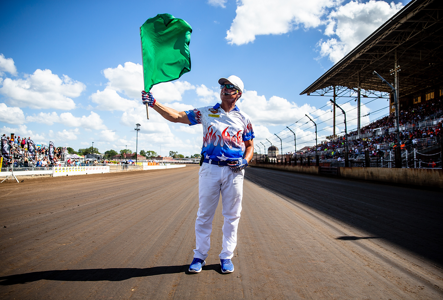 Official flagman Bubba Blackwell holds the green flag lifted by the high winds on the track prior to the start of the American Flat Track Springfield Mile II at the Illinois State Fairgrounds, Sunday, Sept. 2, 2018, in Springfield, Ill. [Justin L. Fowler/The State Journal-Register]
