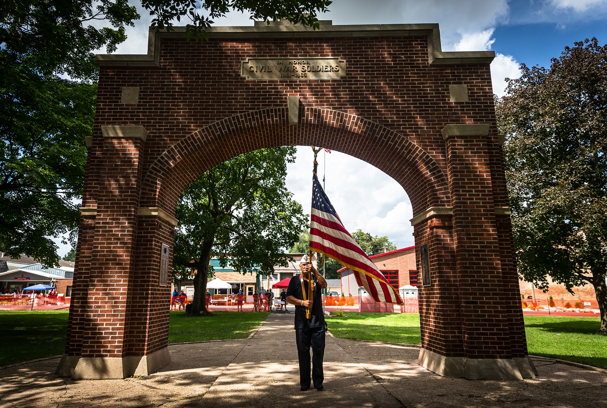 Marine Corps. Veteran Norm Flowers carries the American Flag under the newly refurbished Greenview WWI Monument Arch during a ceremony to rededicate the arch as the Greenview Veterans Memorial during the 50th Greenview Labor Day Celebration in Greenview Community Park, Sunday, Sept. 2, 2018, in Greenview, Ill. The arch was originally built in 1920 and had to have 500 bricks replaced in the restoration process that was paid for by donations from the community and a grant from Landmarks Illinois' World War I Monument Preservation Grant program. [Justin L. Fowler/The State Journal-Register]