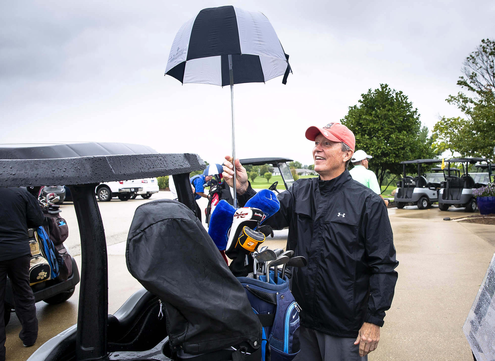 Ed Gvazdinskas deploys an umbrella over his golf clubs before starting out for the 28th annual Friend-in-Deed golf outing Friday, Sept. 7, 2018 at Panther Creek Country Club in Springfield, Ill. Close to 130 golfers signed up for this year's event, which raises money for the annual Christmas charity. [Rich Saal /The State Journal-Register]