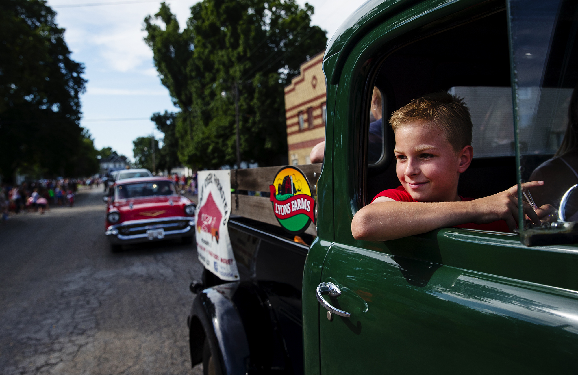 Jack Legner watches out the window a 1949 Dodge pick-up truck from Lyons Farms as he rides along during the 50th Annual Greenview Labor Day Celebration Monday, Sept. 3, 2018. [Ted Schurter/The State Journal-Register]