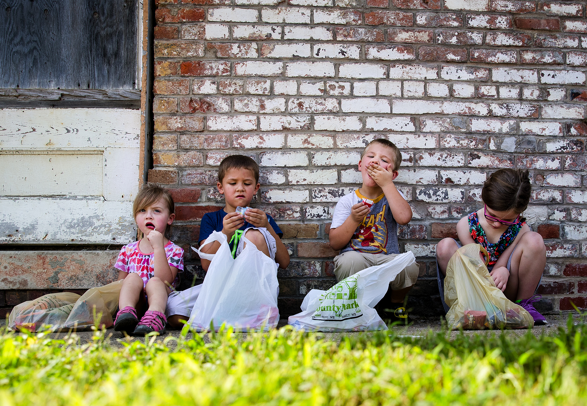 Genevieve Ramos, left, brothers Kyann and Asher Johnson, and Madison Swarts take a break from the parade to sample some of their candy in the shade during the 50th Annual Greenview Labor Day Celebration Monday, Sept. 3, 2018. [Ted Schurter/The State Journal-Register]