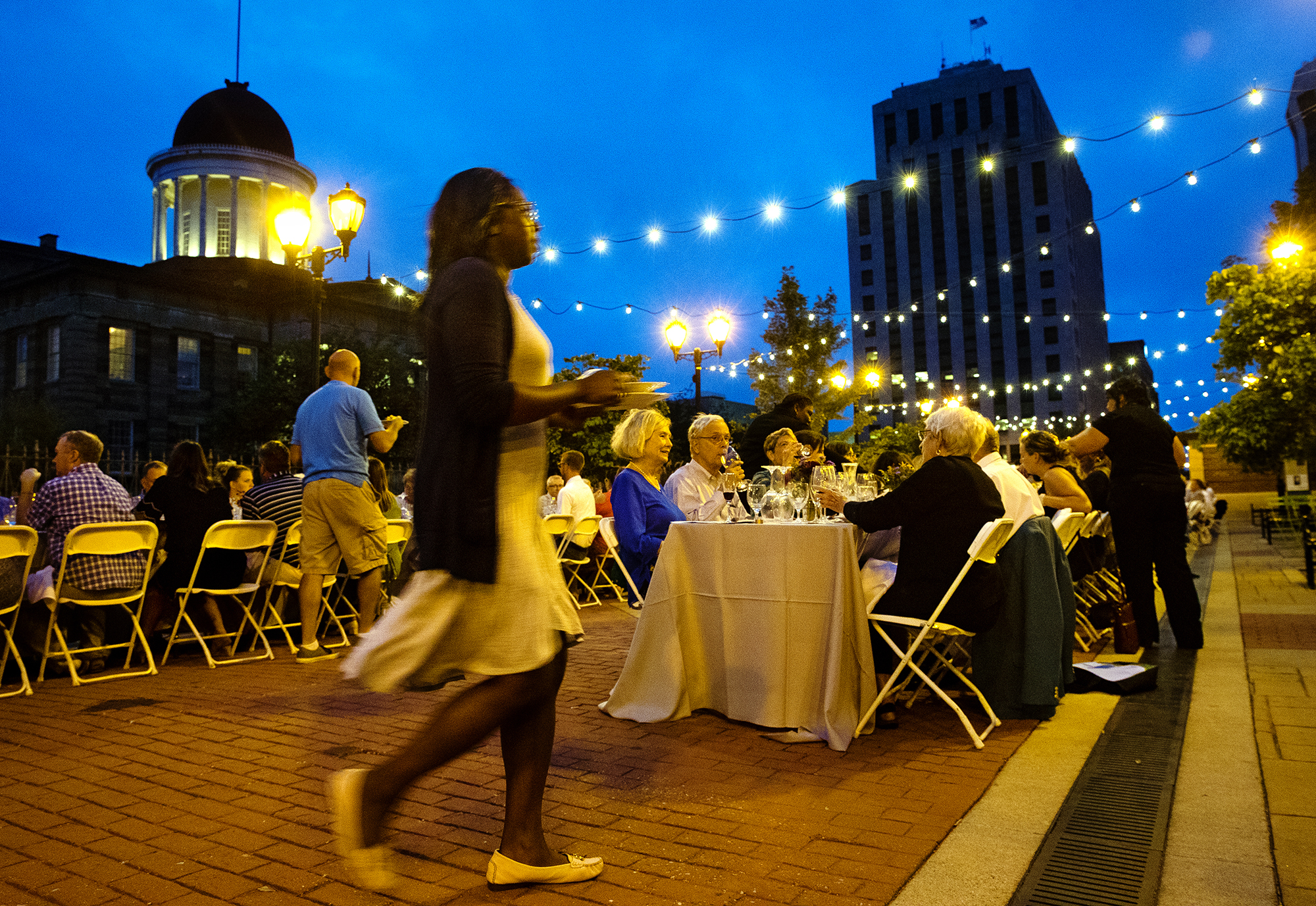 Diners gather under the fading evening light during the 3rd Annual Friends of the Market Street Dinner on the Old State Capitol Plaza Thursday, Sept. 6, 2018. Two hundred seats were available for the four course meal created with food from vendors of the Downtown Farmer's prepared by local chefs. [Ted Schurter/The State Journal-Register]