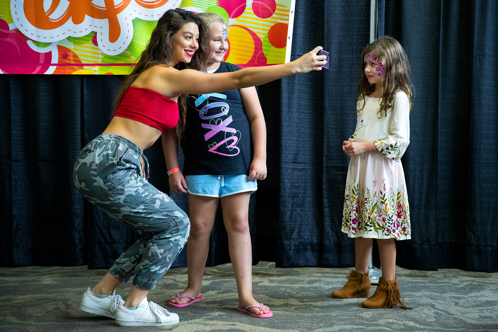 """Actress Kira Kosarin, known for her role as Phoebe Thunderman on the Nickelodeon series """"The Thundermans,"""" poses for a selfie with Kadence White as Anna Flatt looks on during the Springfield Kidz Expo at the Bank of Springfield Center Saturday, Sept. 8, 2018. The event featured face painting, balloon animals, pictures with costume characters, magicians and on-going entertainment throughout the day. [Ted Schurter/The State Journal-Register]"""