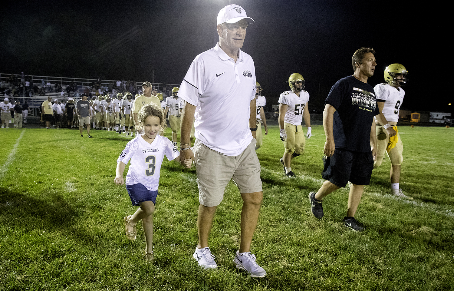 Escorted by his granddaughter Julia, Sacred Heart-Griffin head coach Ken Leonard crosses the field to shake hands with Southeast head coach Matt Lauber and the Spartans after the Cyclones won at Southeast High School Friday, Sept. 14, 2018. [Ted Schurter/The State Journal-Register]