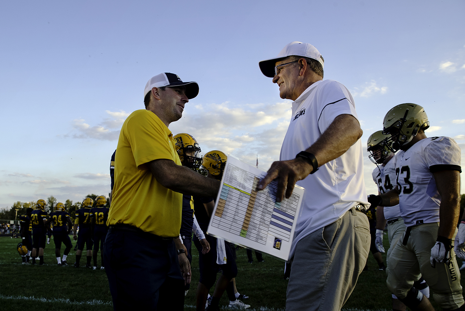 Southeast head coach Matt Lauber  and Sacred Heart-Griffin head coach Ken Leonard greet each other at midfield before the game at Southeast High School Friday, Sept. 14, 2018. [Ted Schurter/The State Journal-Register]