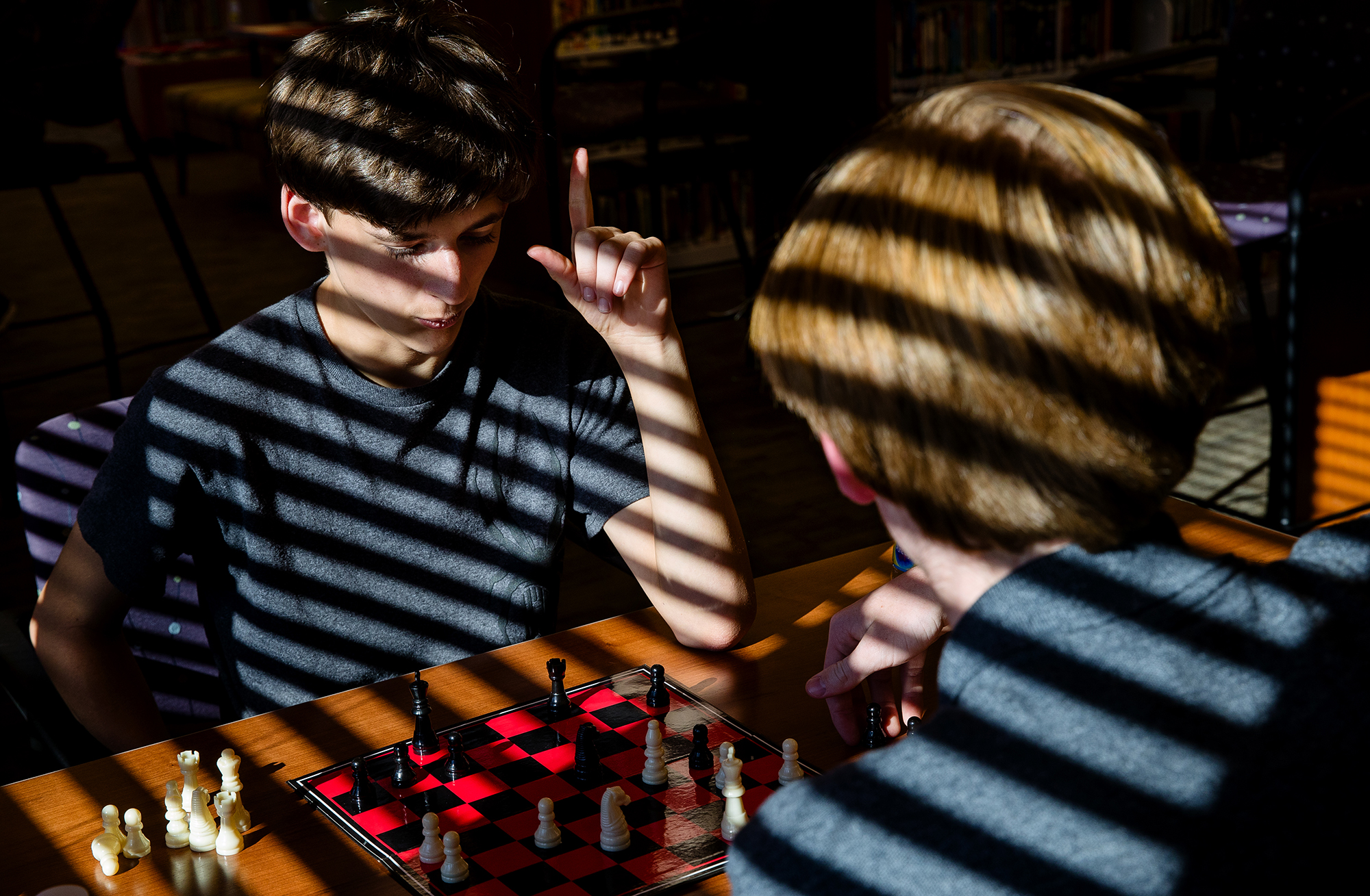 Bisected by the shadows cast by sunlight coming through the window blinds, Tyler Vinger, left, prepares to make his next move as he and Gage Gathman play chess at the Williamsville Public Library Thursday, Sept. 13, 2018. The library makes boards available to players of any age Thursday from 3:30 p.m. to 6 p.m.. The library will schedule a tournament later in the fall if enough participants are interested. [Ted Schurter/The State Journal-Register]