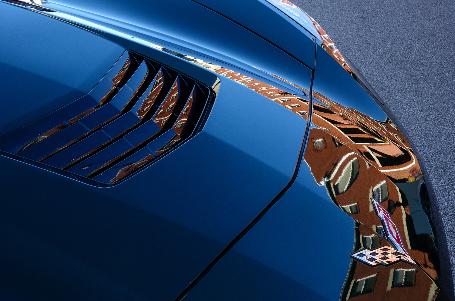 The Lincoln Square Apartments are distorted as they are reflected on the sculpted hood of a Chevrolet Corvette during the 17th Annual International Route 66 Mother Road Festival Sunday, Sept. 23, 2018. [Ted Schurter/The State Journal-Register]