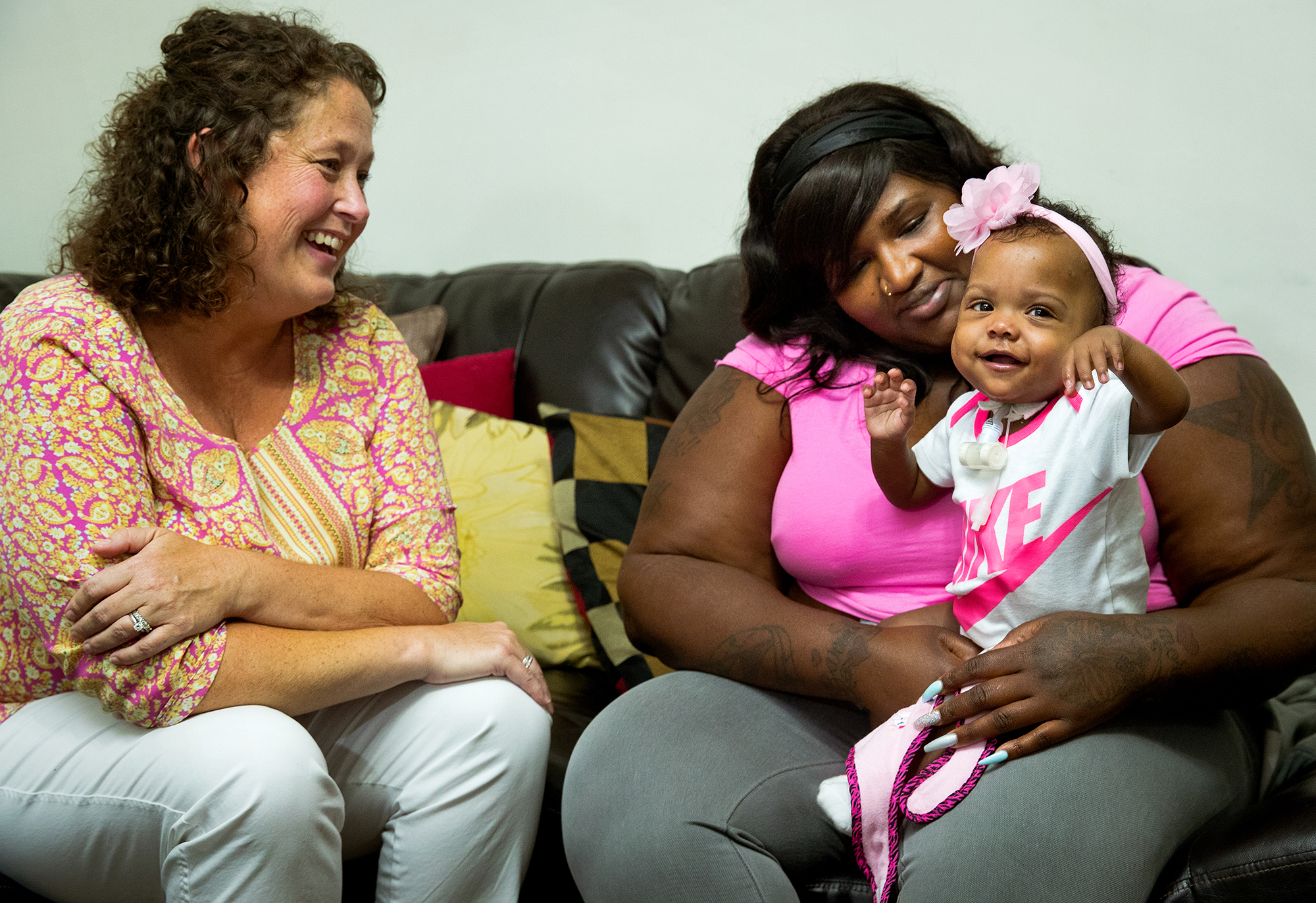 Katie Stauffer RN, head nurse of HSHS St. John's Children's Hospital's Beyond the NICU program, laughs as Tracy Williams' 14-month-old daughter Triniti smiles and claps while sitting on her lap during an interview Friday, Sept. 14, 2018. Triniti was born premature and spent months in the neonatal intensive care unit and receives follow-up care and monitoring through the new program. [Ted Schurter/The State Journal-Register]