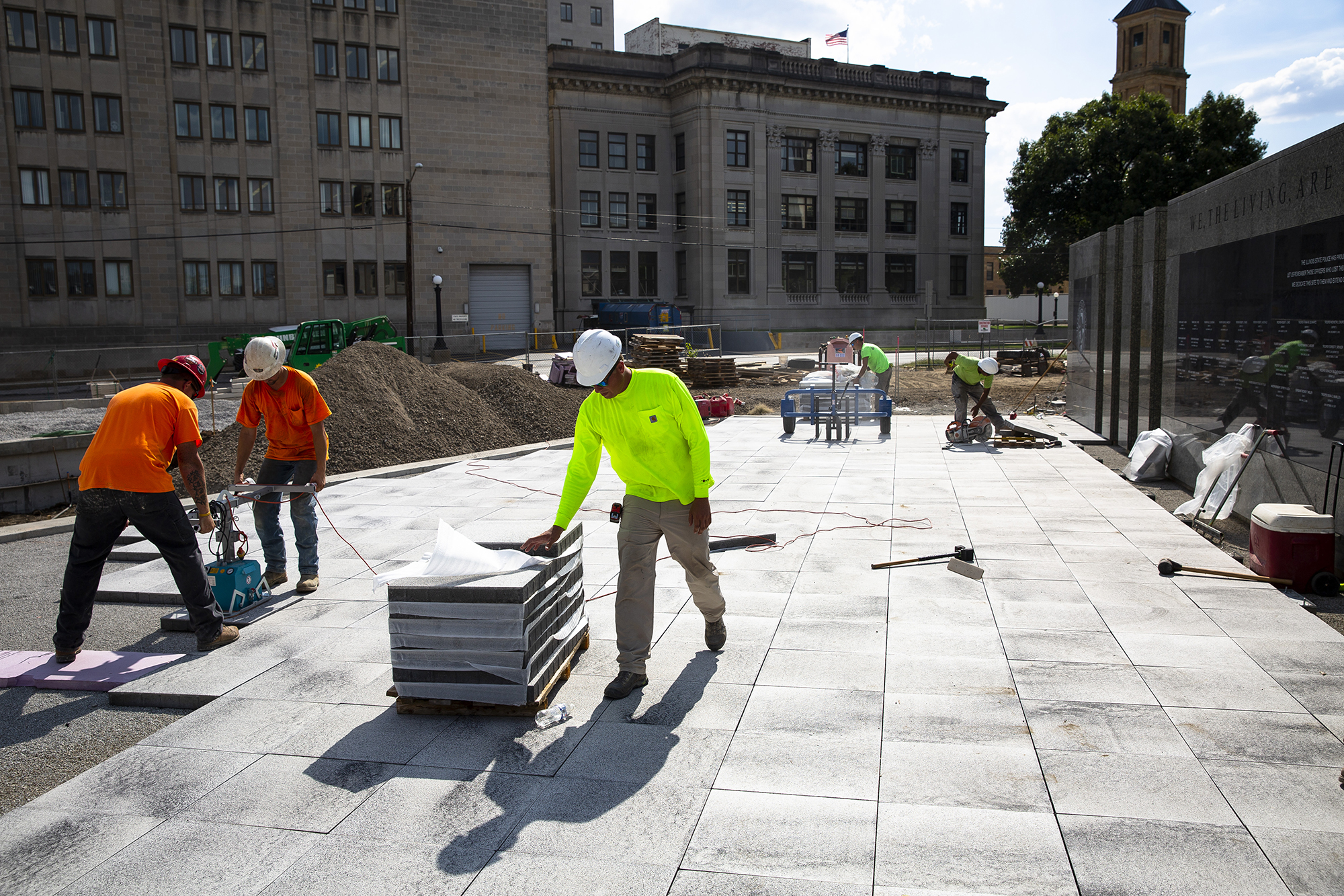 Workers from Cothren's Custom Hardscapes in Decatur place paver blocks on the north plaza of the Illinois State Police Memorial Park, under construction Tuesday, Sept. 18, 2018 on Lawrence Avenue between Sixth and Seventh streets in Springfield, Ill. The $2.5 million project is being paid for by donations from state troopers, the public and businesses, and will include a granite memorial wall that will list the names of State Police troopers who have been killed in the line of duty, sculptures, and a water feature. According to Ron Cooley, president of the Illinois State Police Heritage Foundation, the park will be officially dedicated Oct. 2. [Rich Saal/The State Journal-Register]
