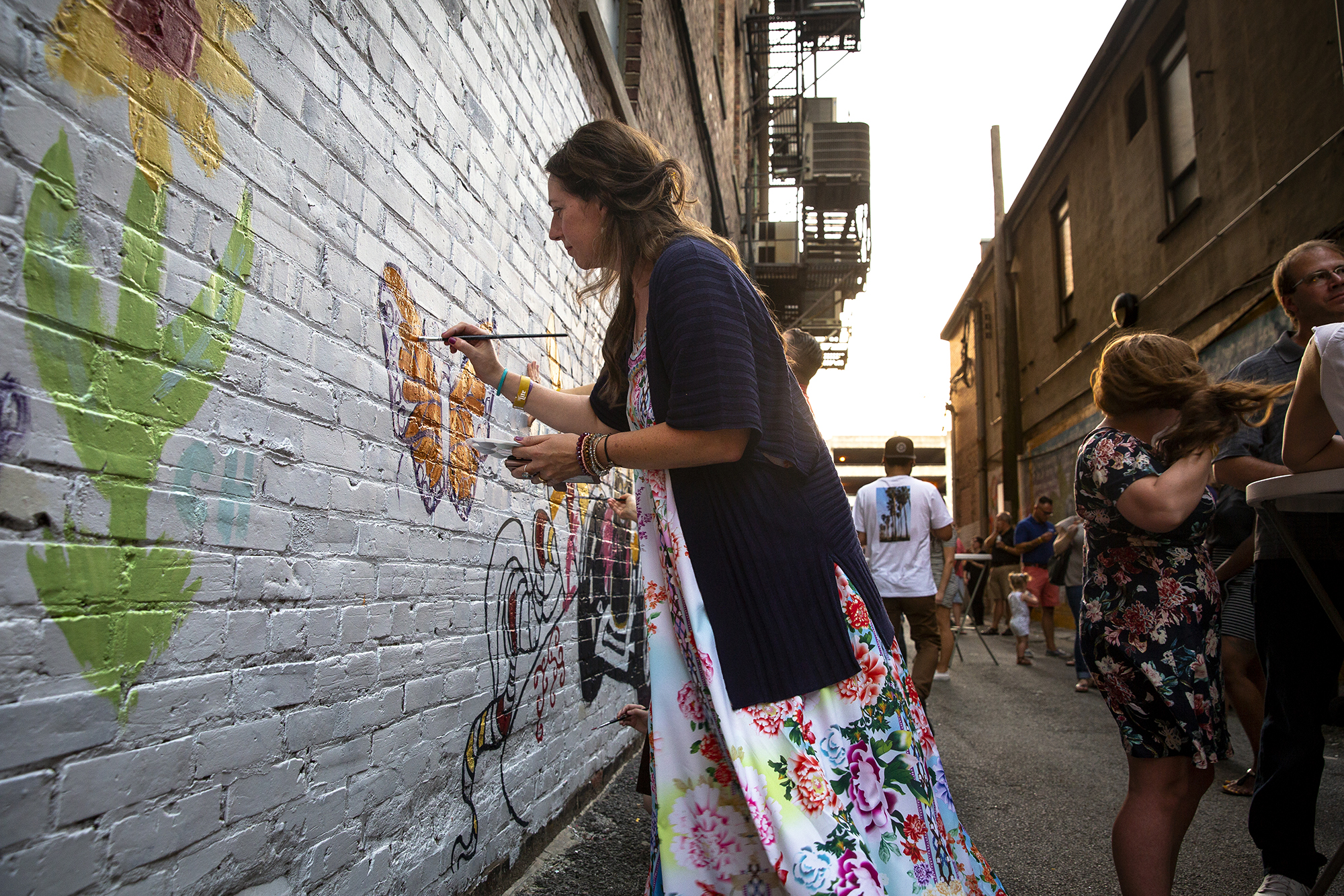 Anna Richie adds a butterfly to the community-created mural at Downtown Springfield Inc.'s Art Alley II pop-up event Thursday, Sept. 20, 2018 in the alley between Fourth and Fifth streets near the Old State Capitol Springfield, Ill. This year's featured muralists are Jen Santarelli, Jeff Curtis Williams and artists from DEMO Project. Proceeds from the event benefit future public art projects, part of DSIÕs program for downtown revitalization. [Rich Saal/The State Journal-Register]
