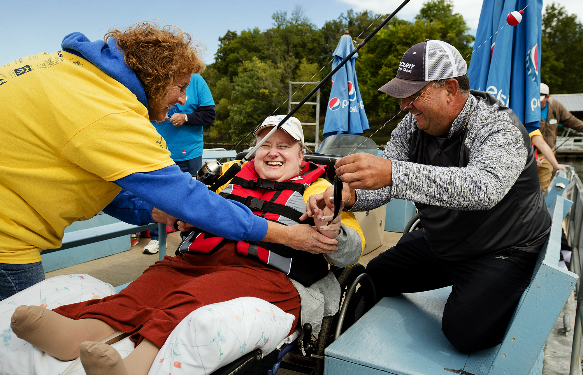 Rhonda Roeper smiles and laughs as she touches a fish she caught during the Capital City Chapter of Fishing Has No Boundaries second annual event at the TRN Club Saturday, September 22, 2018. The organization helps people with disabilities participate in outdoor  recreational activities.  [Ted Schurter/The State Journal-Register]